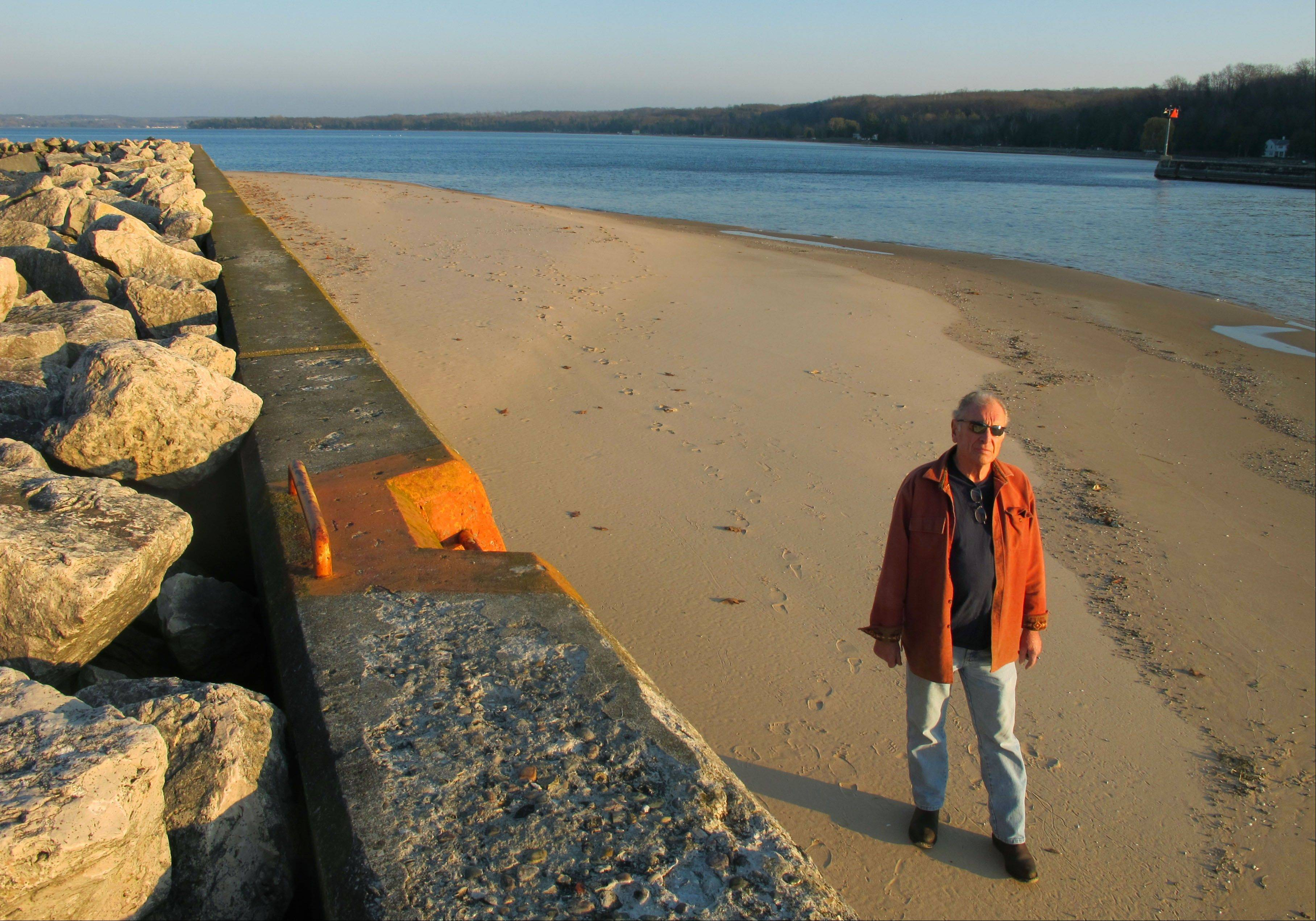 Jim Simons walks along a sand bar, exposed by low water levels, on the Portage Lake channel that leads to Lake Michigan at Onekama, Mich.