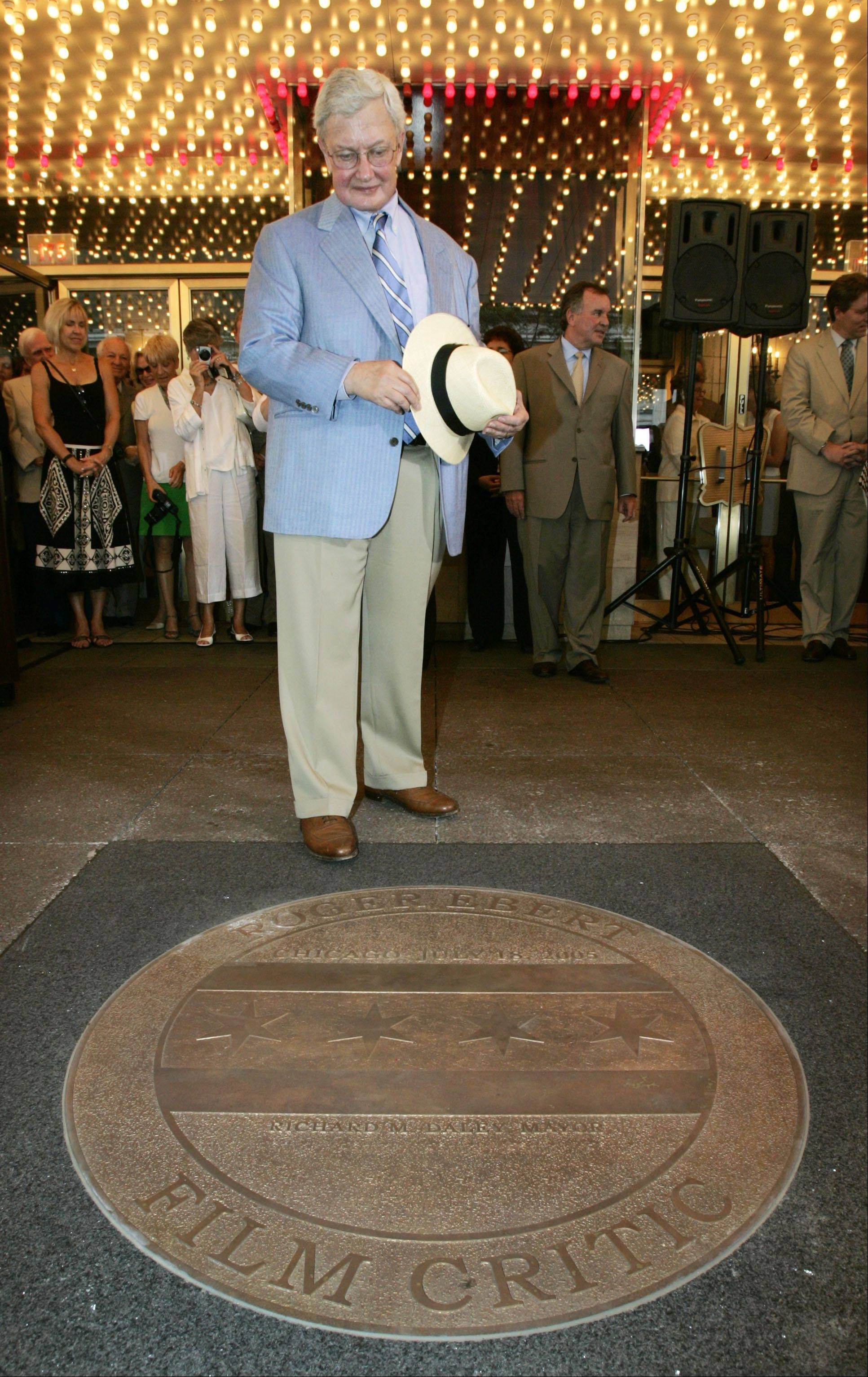 Roger Ebert admires a sidewalk medallion bearing his name that was unveiled under the marquee of the Chicago Theatre on Monday, July 18, 2005, during Chicago's tribute to the hometown film critic. Ebert, 63, became the film critic for the Chicago Sun-Times in 1966 and a decade later became the first film critic to receive a Pulitzer Prize for arts criticism.