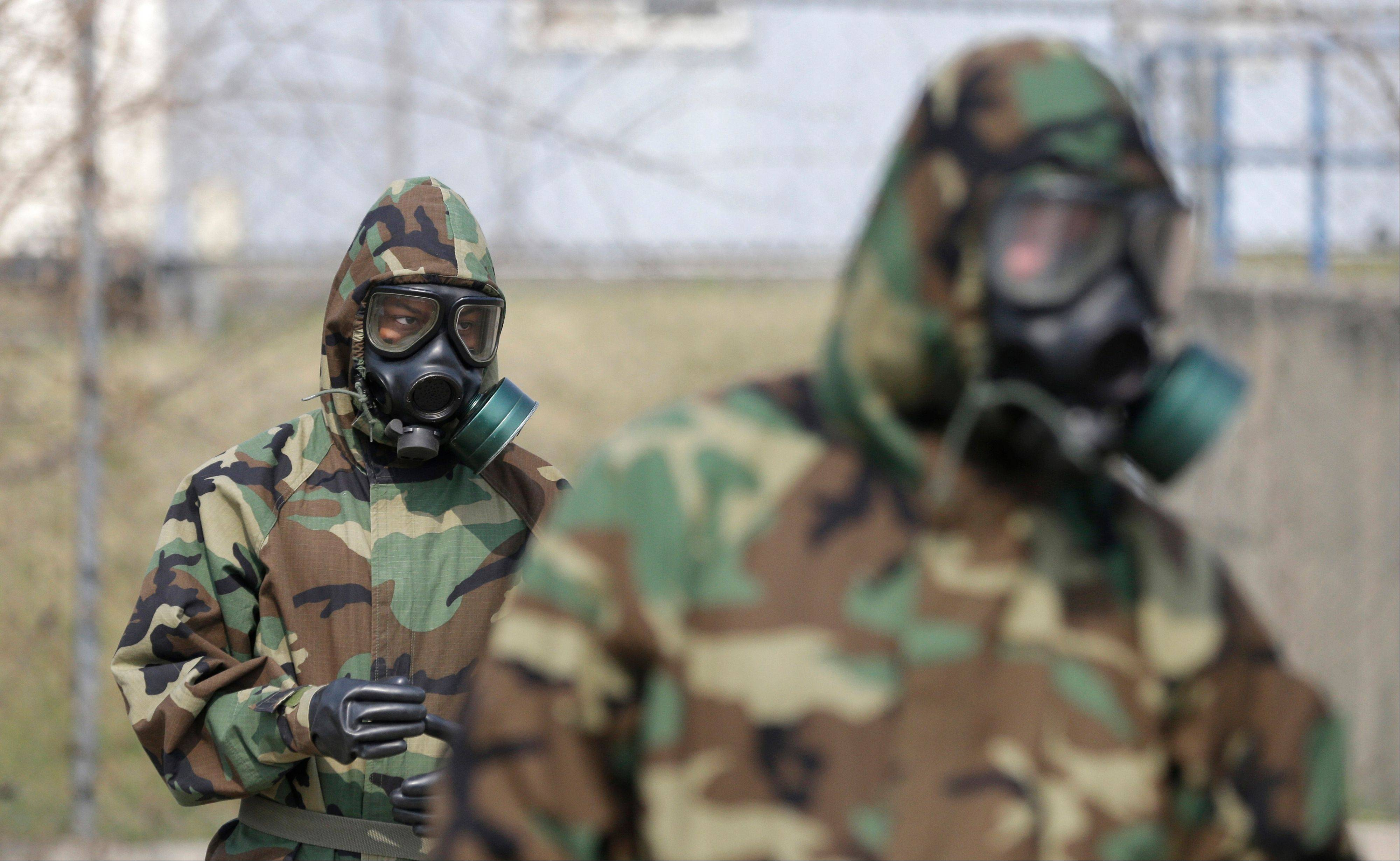 Soldiers of the U.S. Army 23rd chemical battalion wear gas masks while attending a demonstration of their equipment during a ceremony to recognize the battalion's official return to the 2nd Infantry Division based in South Korea at Camp Stanley in Uijeongbu, north of Seoul, Thursday.