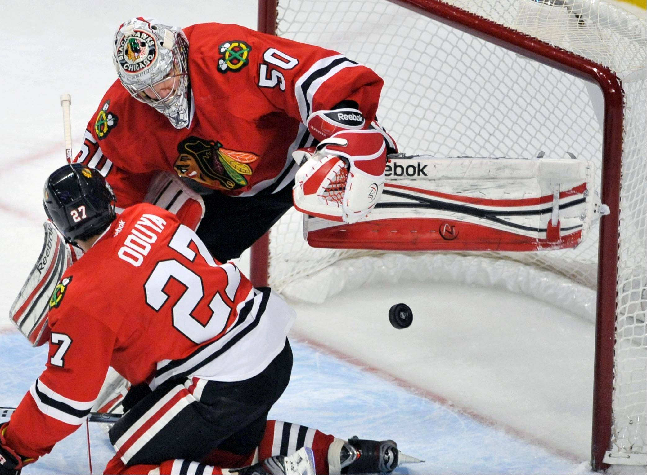 Corey Crawford makes a save against the St. Louis Blues while Blackhawks teammate Johnny Oduya looks on during the first period of an NHL hockey game in Chicago, Thursday, April 4, 2013.