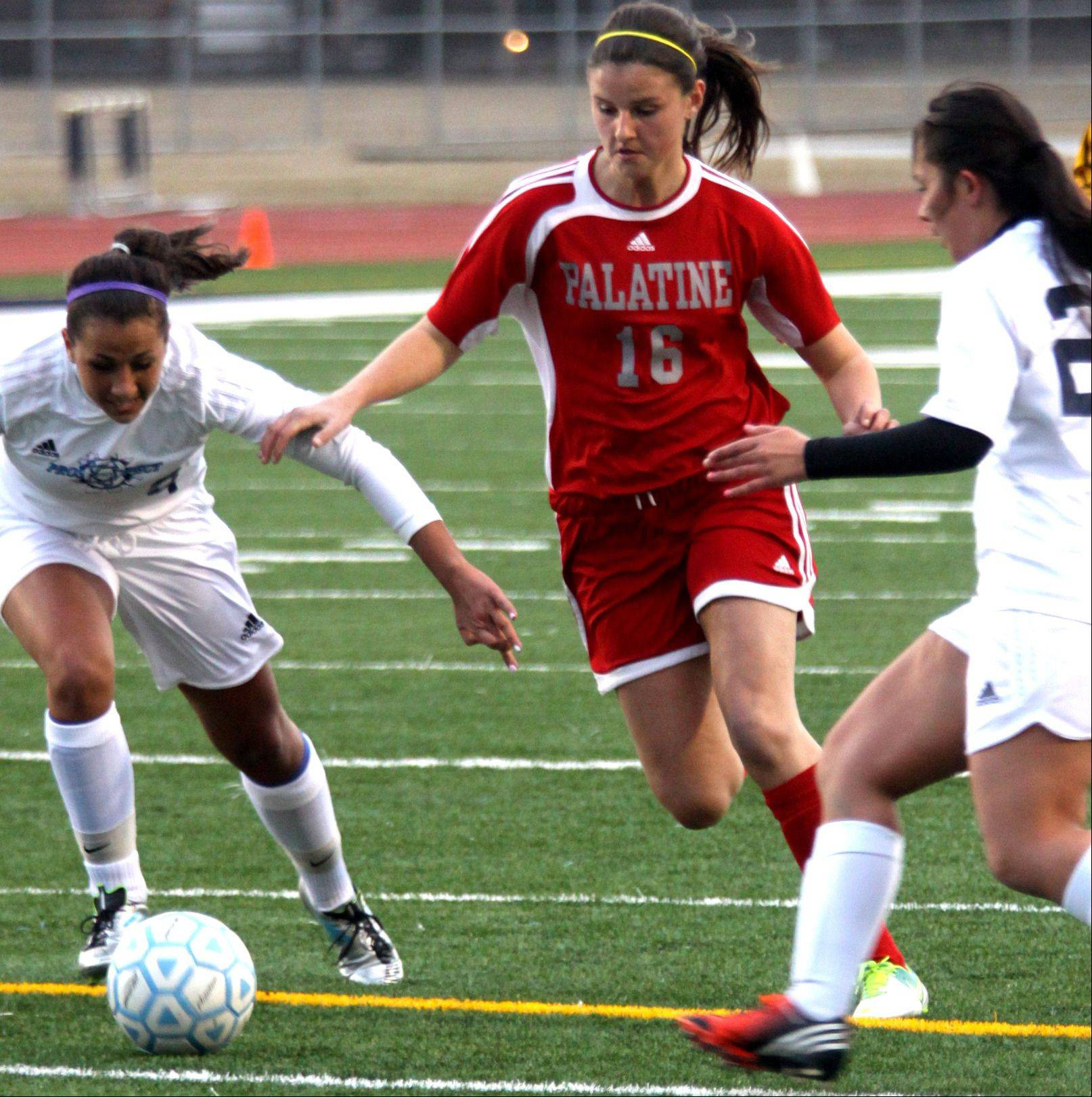 Prospect's Kristen Frasco, left, and Elena Cukurs, right, close in on Palatine's Erin Mayer, center, during Thursday's game at George Gattas Memorial Stadium in Mount Prospect.