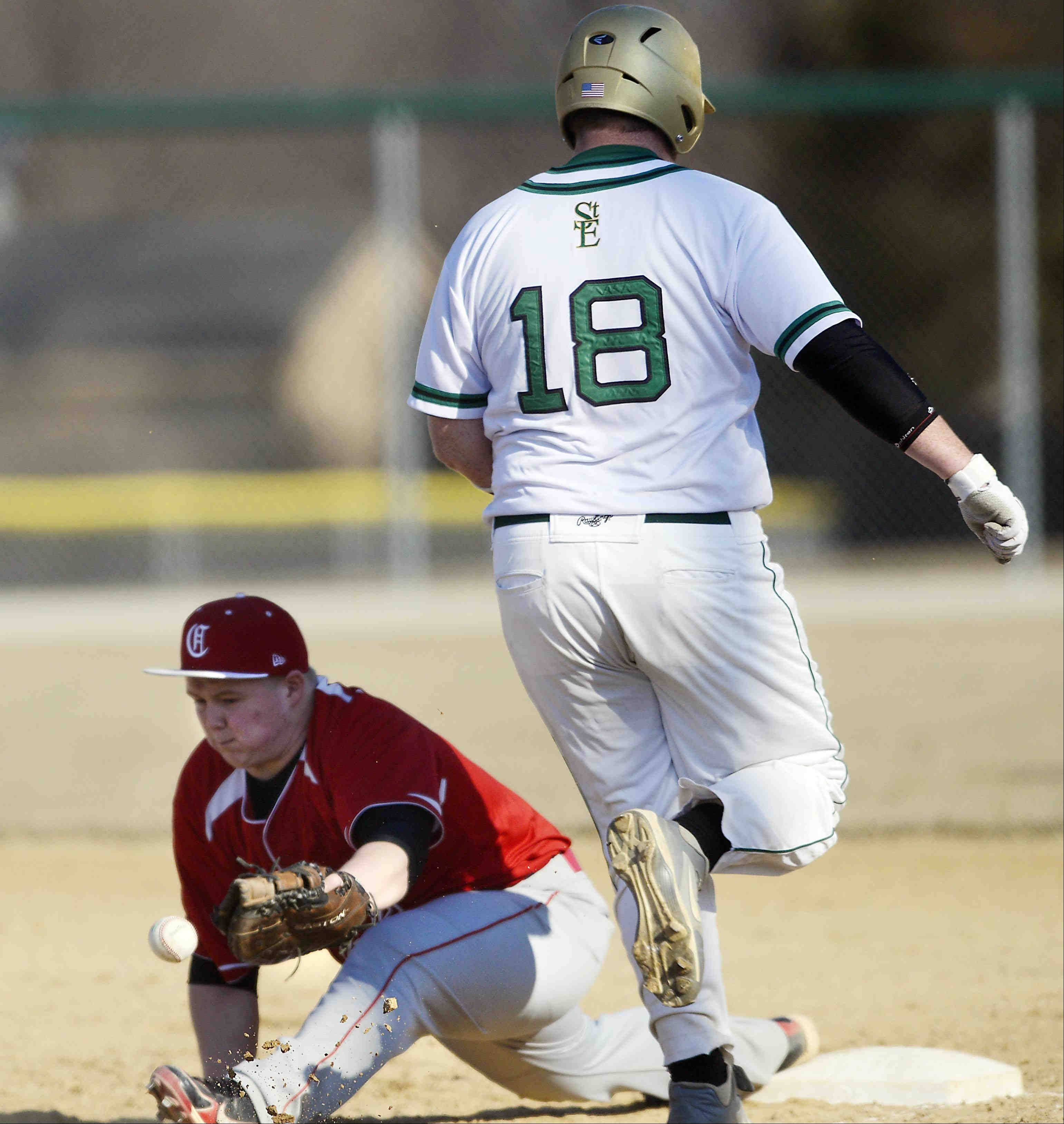 Aurora Christian first baseman Tristin Withrow can't reach a wide throw from third baseman Dustin Barrett as St. Edward's Zach West reaches base safely in the first inning Thursday in Elgin.