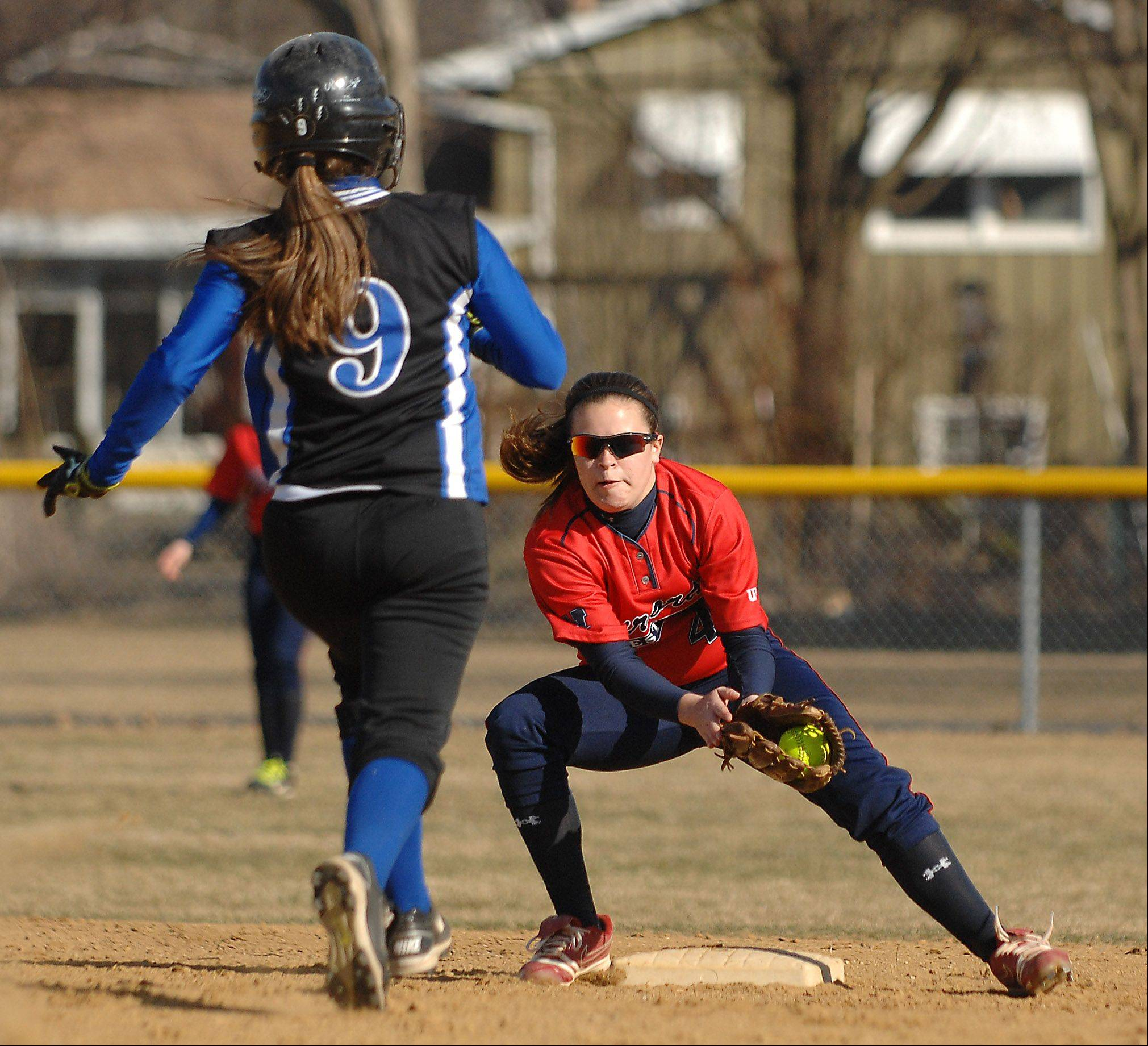 West Aurora's Taylor Podshweit prepares to tag out Rosary's Emma Molenhouse on a stolen base attempt during Thursday's game in Aurora.