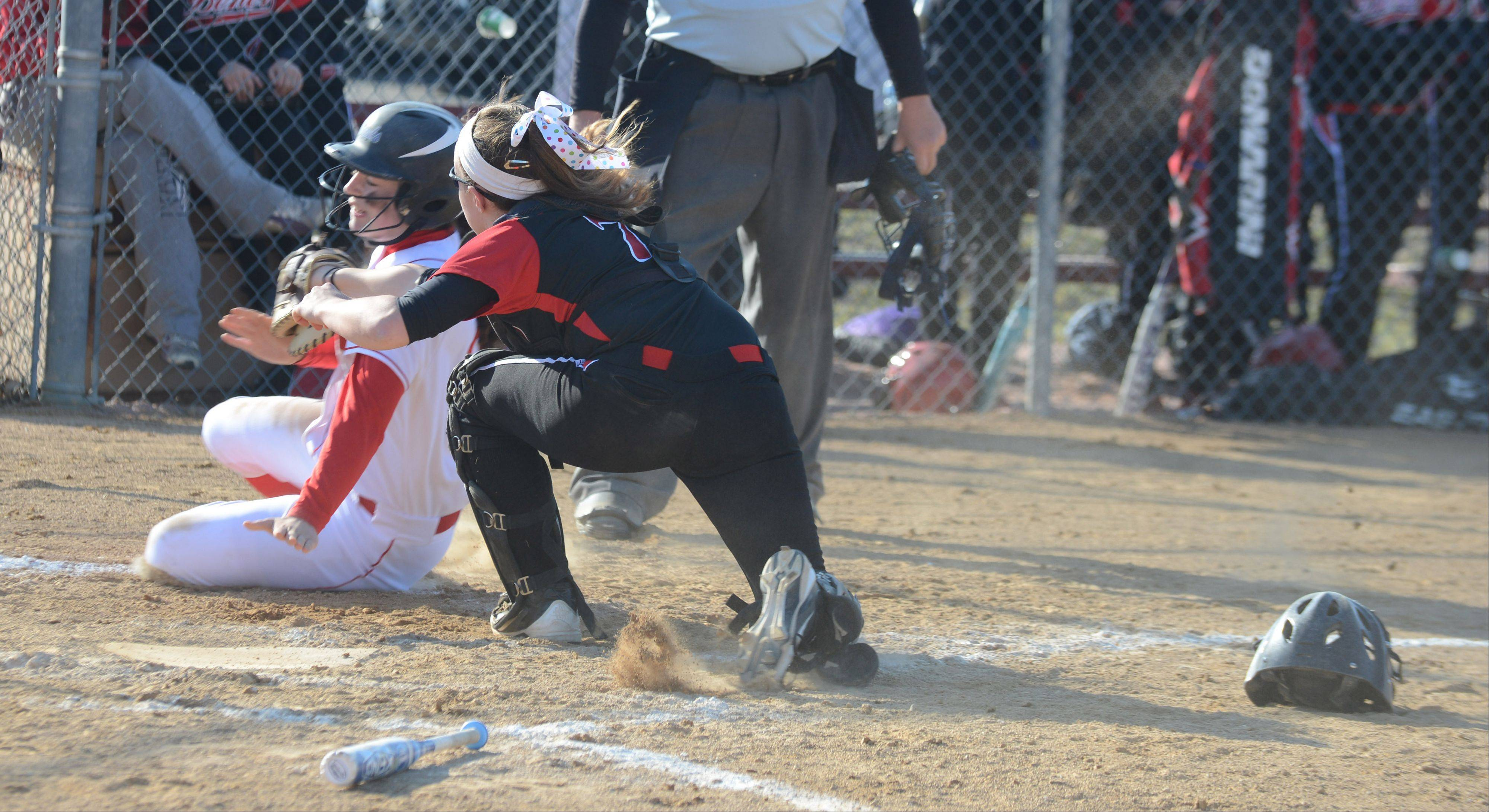 Lisa Tassi of Naperville Central gets tagged out at home by Erin Cohoon of Benet. This took place during the Naperville Central at Benet softball game Thursday.