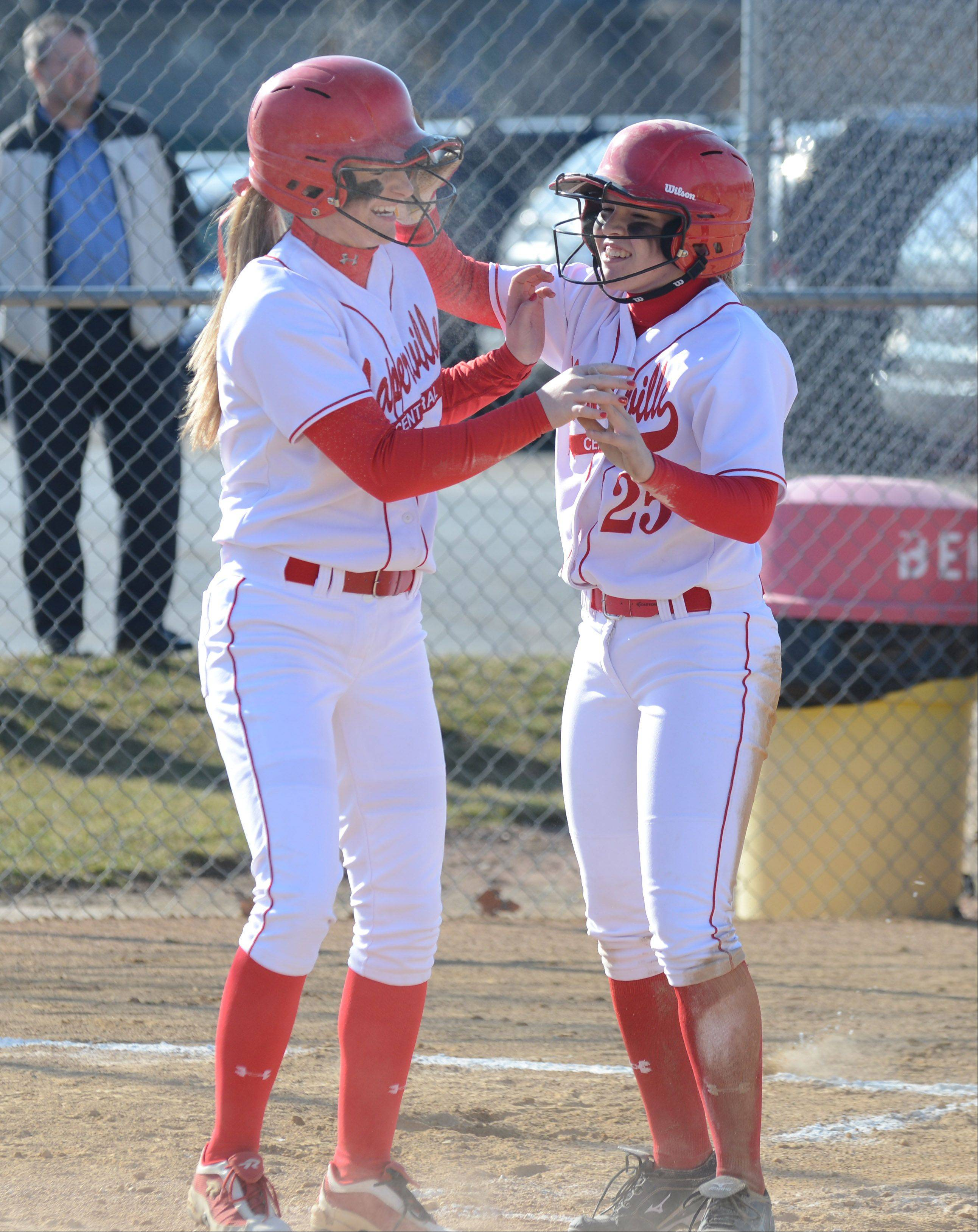 Megan Nerger,left, and Maddi Doane of Naperville Central celebrate a run during the Naperville Central at Benet softball Thursday in Lisle.