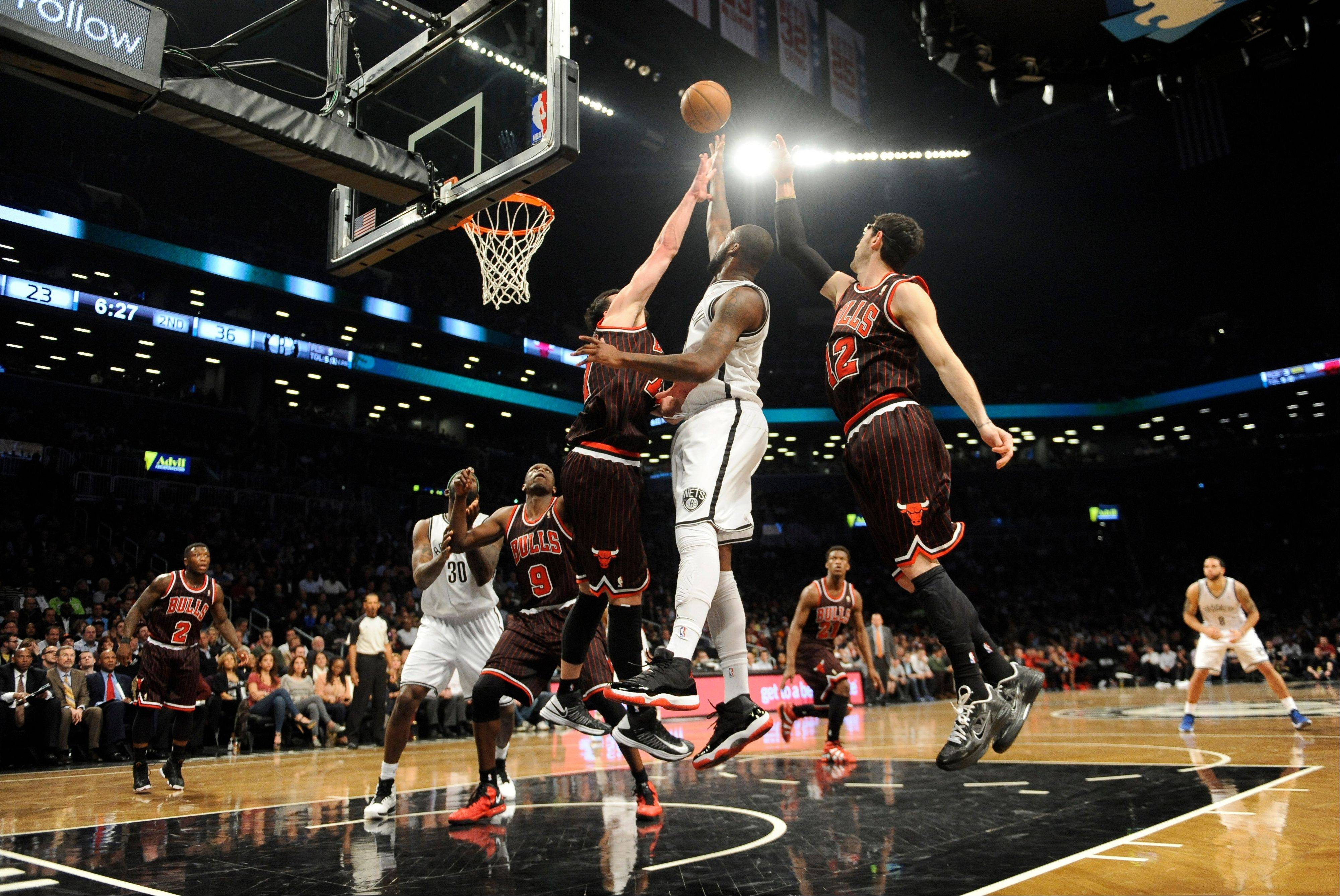 Brooklyn Nets' Andray Blatche (0) shoots between Chicago Bulls' Vladimir Radmanovic (77) and Kirk Hinrich (12) in the first half of an NBA basketball game on Thursday, April 4, 2013, at Barclays Center in New York.
