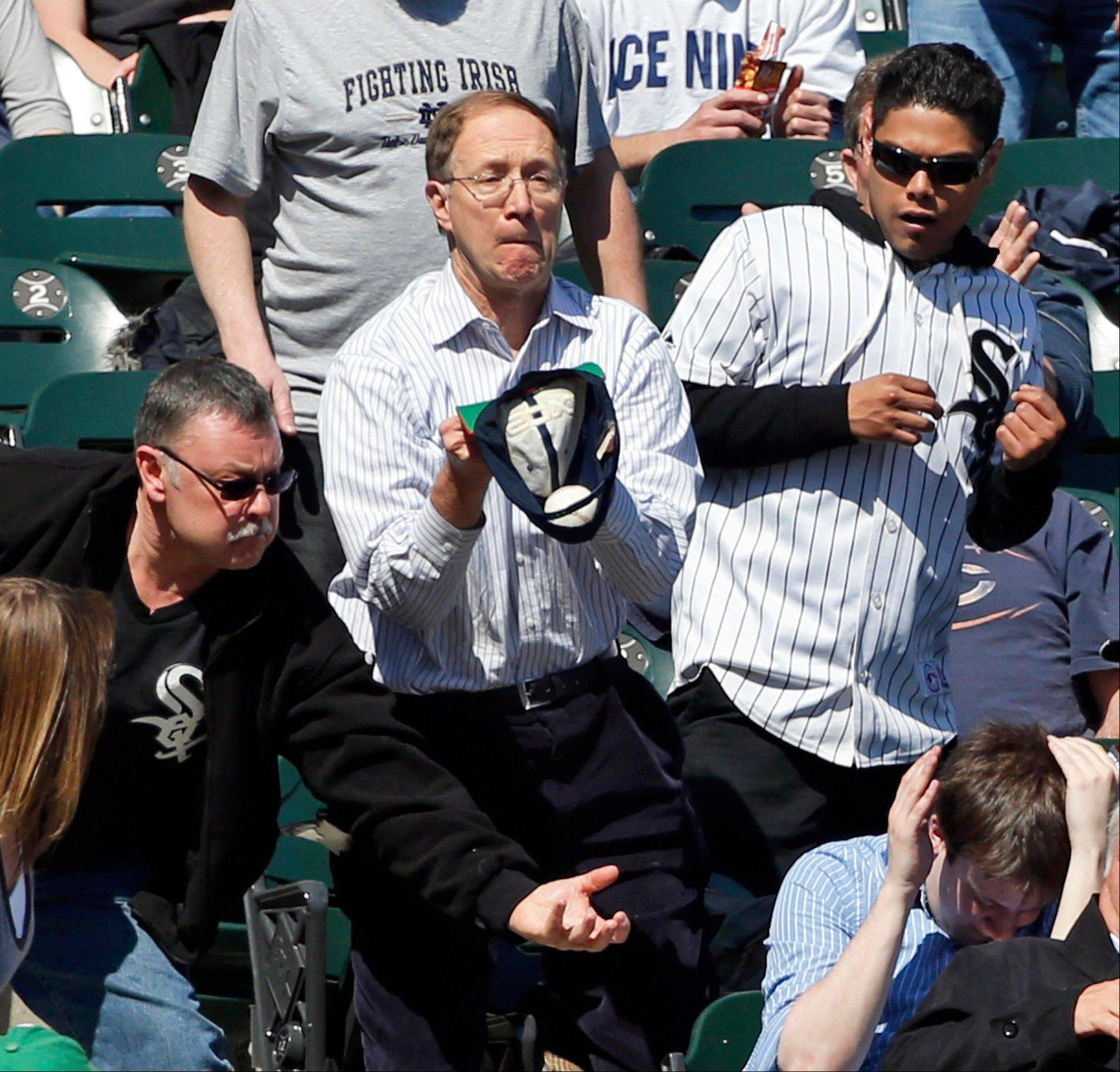 A fan catches a foul ball with his ball cap during the fifth inning of Kansas City's victory over the White Sox on Thursday at U.S. Cellular Field.