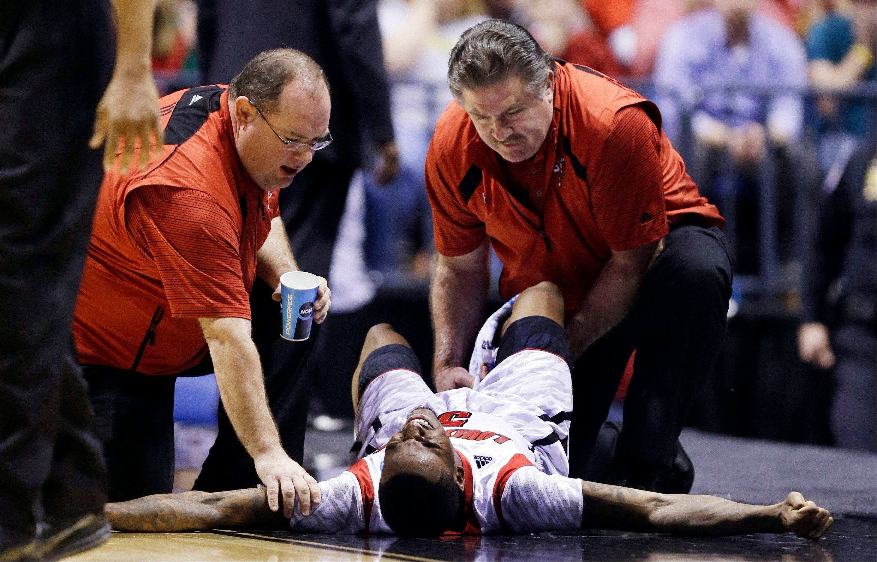 AP10ThingsToSee - Trainers check on Louisville guard Kevin Ware after he broke his leg during the first half of the Midwest Regional final against Duke in an NCAA college basketball tournament, Sunday, March 31, 2013, in Indianapolis.