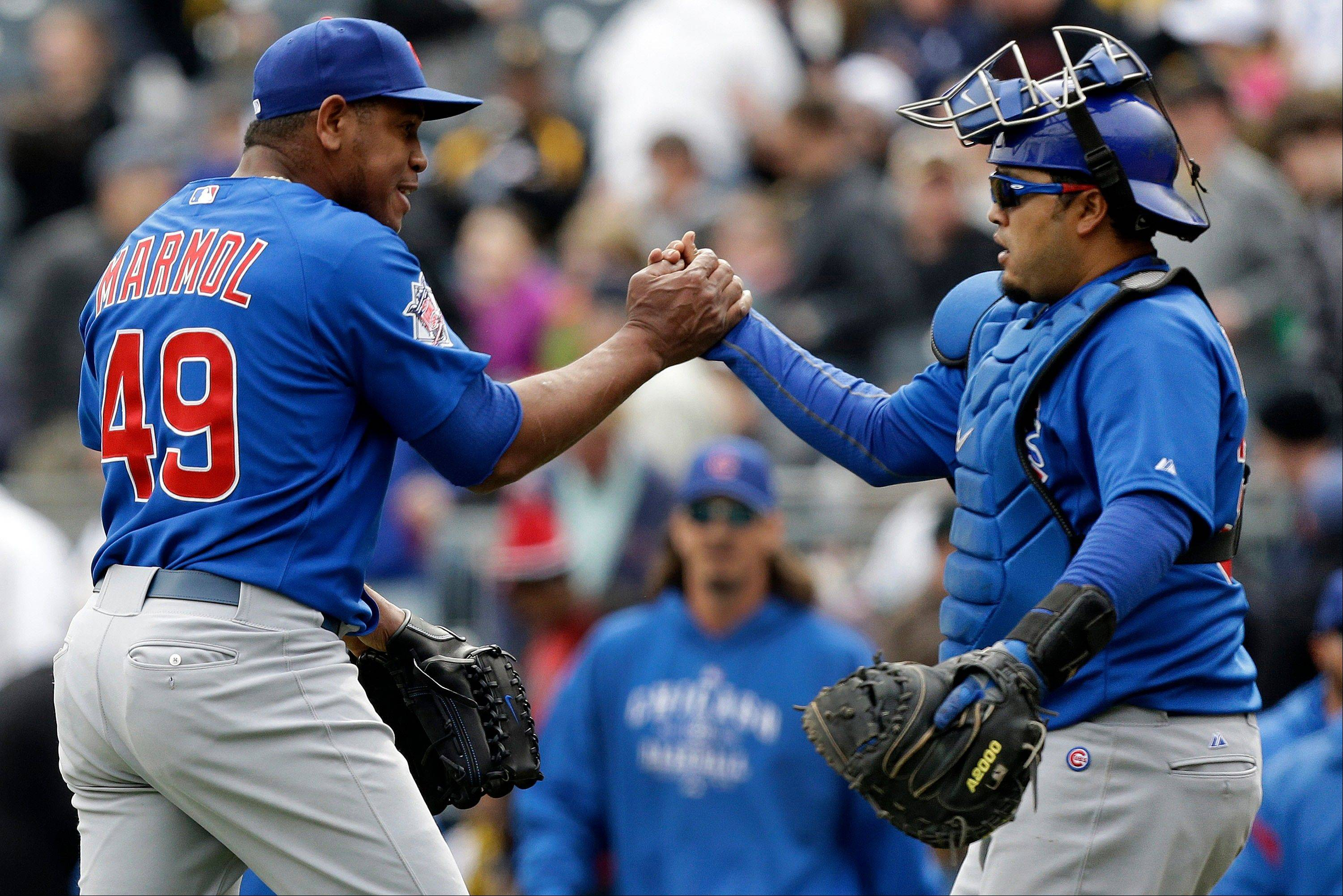 Cubs relief pitcher Carlos Marmol, left, celebrates with catcher Dioner Navarro after getting the final out thanks to a double play in the ninth inning to preserve a 3-2 win over the Pirates in Pittsburgh, Thursday.