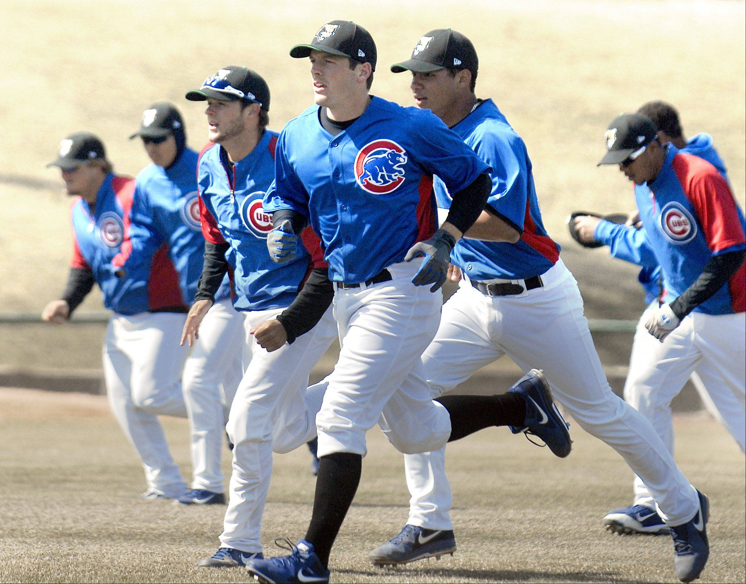 Chadd Krist, center, and Kane County Cougar teammates warm up during practice Tuesday. The Cougars, who are affiliated with the Chicago Cubs, wore their Cubs jerseys during practice.