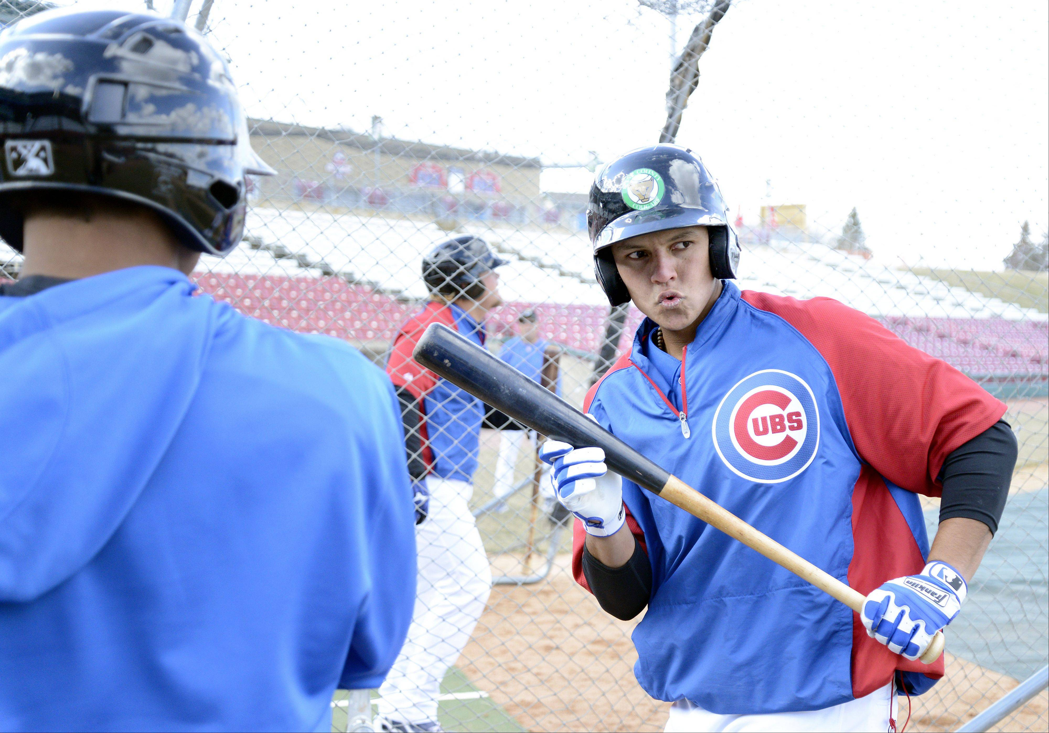 Gioskar Amaya, right, practices his swing in slow motion while getting pointers from Kane County Cougars teammate Marco Hernandez, during practice Tuesday.
