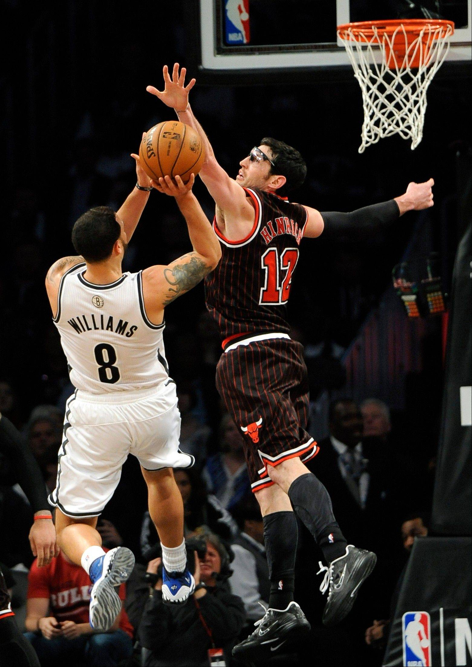 Kirk Hinrich (12) blocks the shot of Brooklyn Nets' Deron Williams (8) in the second half of an NBA basketball game on Thursday, April 4, 2013, at Barclays Center in New York. The Bulls won 92-90.