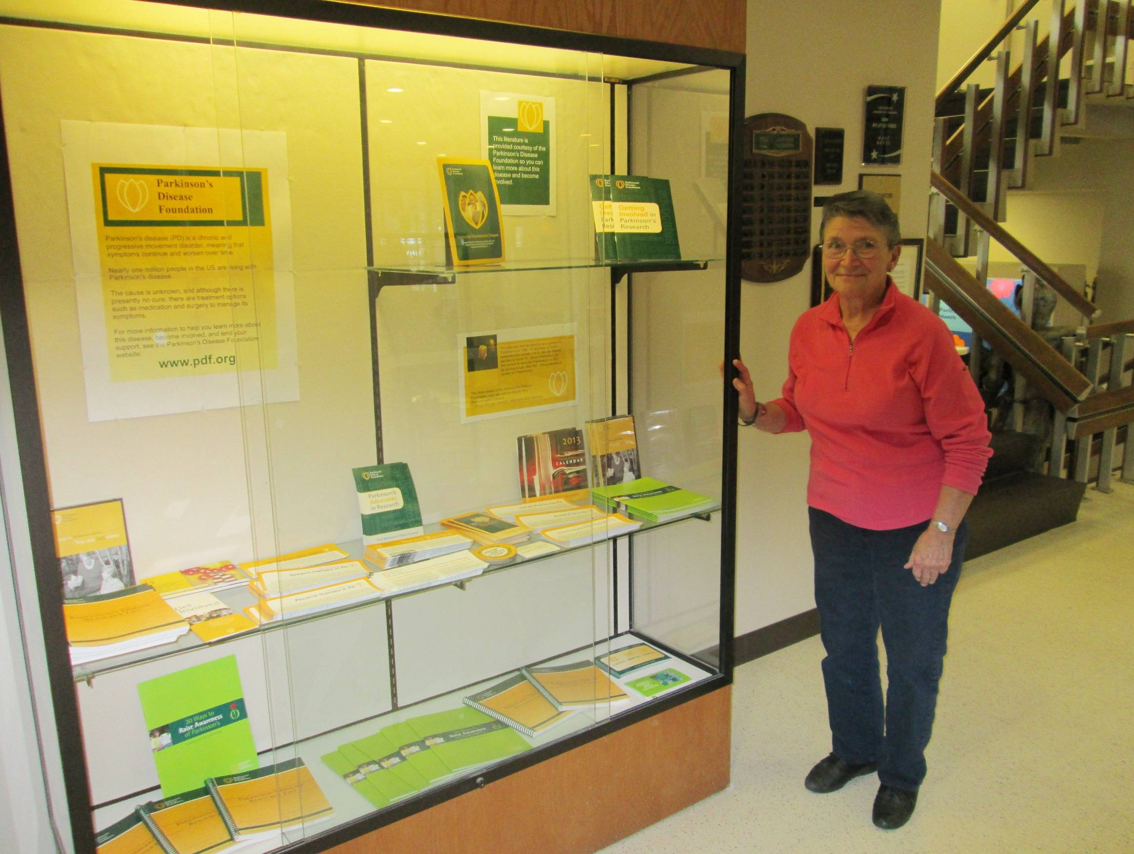 Westchester, IL resident and PDF Research Advocate Rosemary Sammons at the Westchester Public Library with a Parkinson's awareness display featuring free educational resources on the disease.