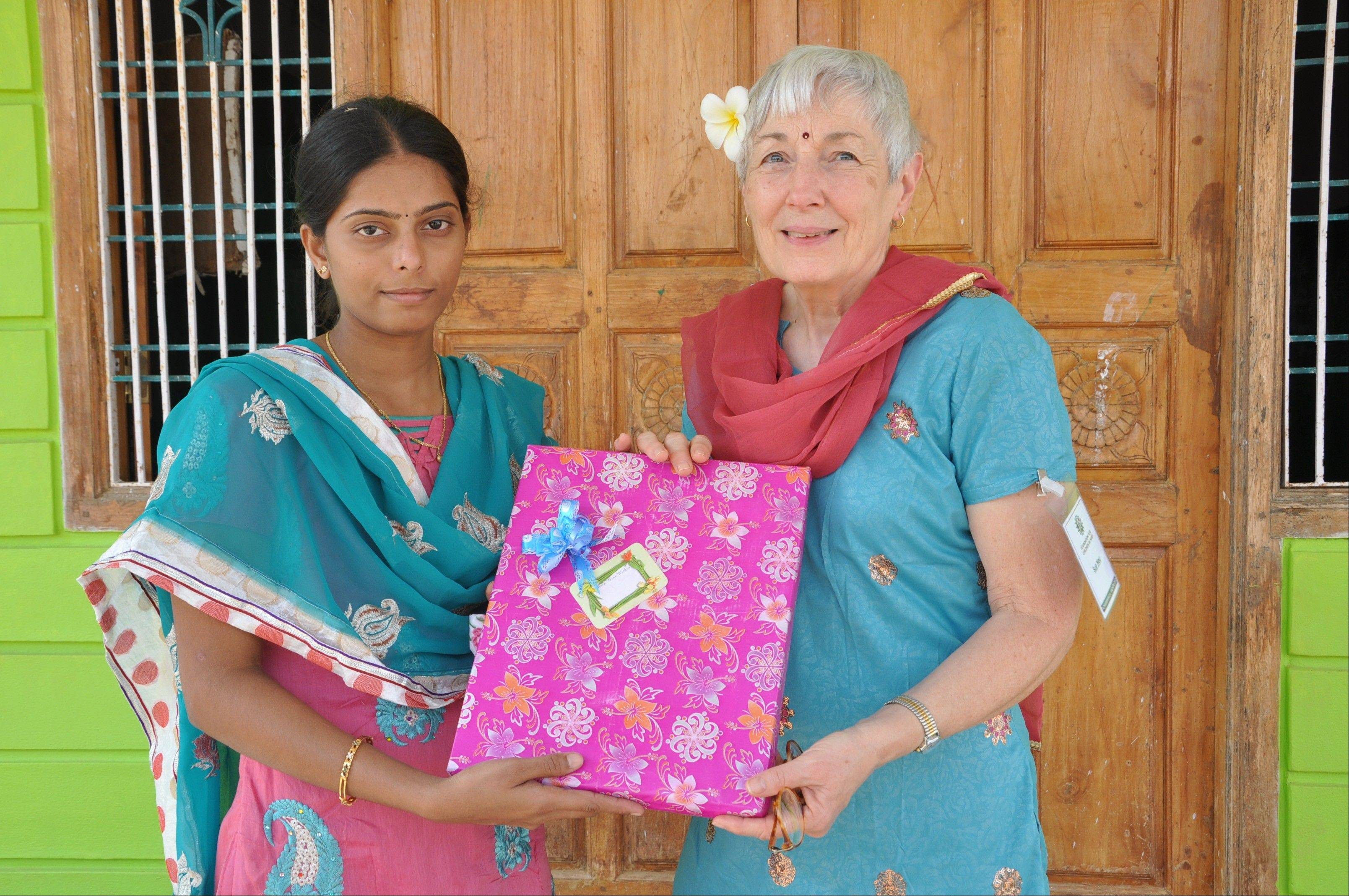 Anitha brings a present to her sponsor Seu Neu of Arlington Heights. She recently graduated to become a registered nurse, like Neu.