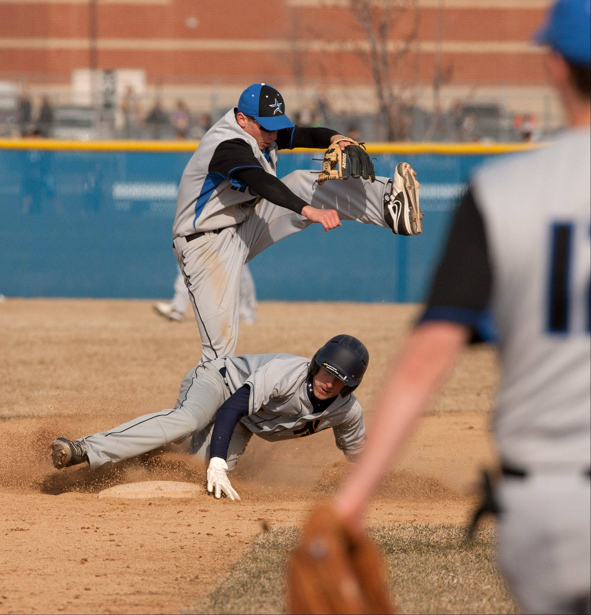 Neuqua Valley�s Josh Piotrowski slides safely into second base under St. Charles North�s Tim Misner, during boys baseball action in Naperville.