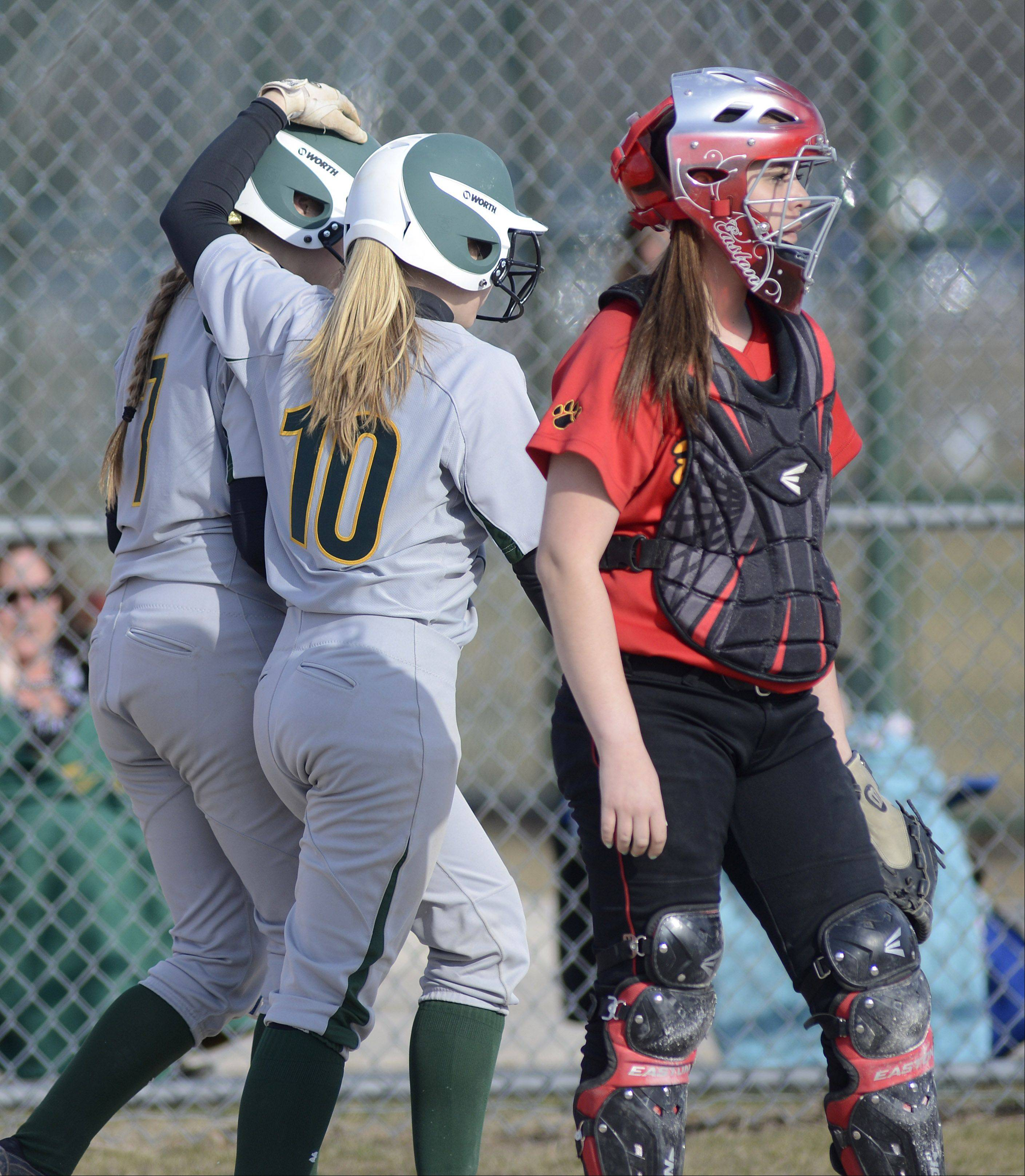 Waubonsie Valley�s Shannon Hohman, left, is congratulated by teammate Amanda Lack after scoring a run as they walk back to the dugout past Batavia catcher Brieann Cruz in the second inning on Friday, April 5. 7