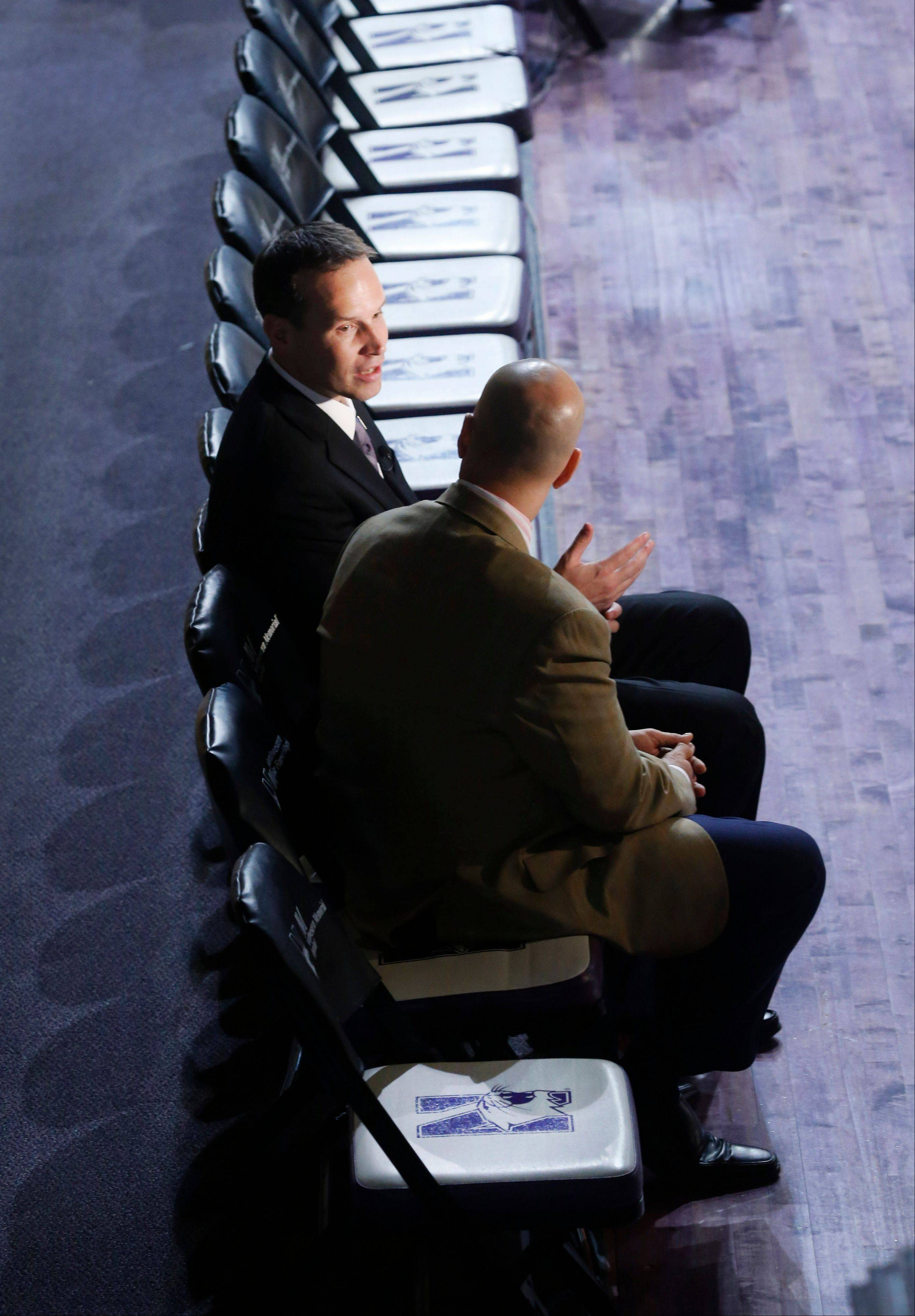 Chris Collins, top, gives a television interview on the Northwestern University bench after he was named the new men's basketball coach at a news conference, Tuesday, April 2, 2013, in Evanston, Ill. (AP Photo/Charles Rex Arbogast)
