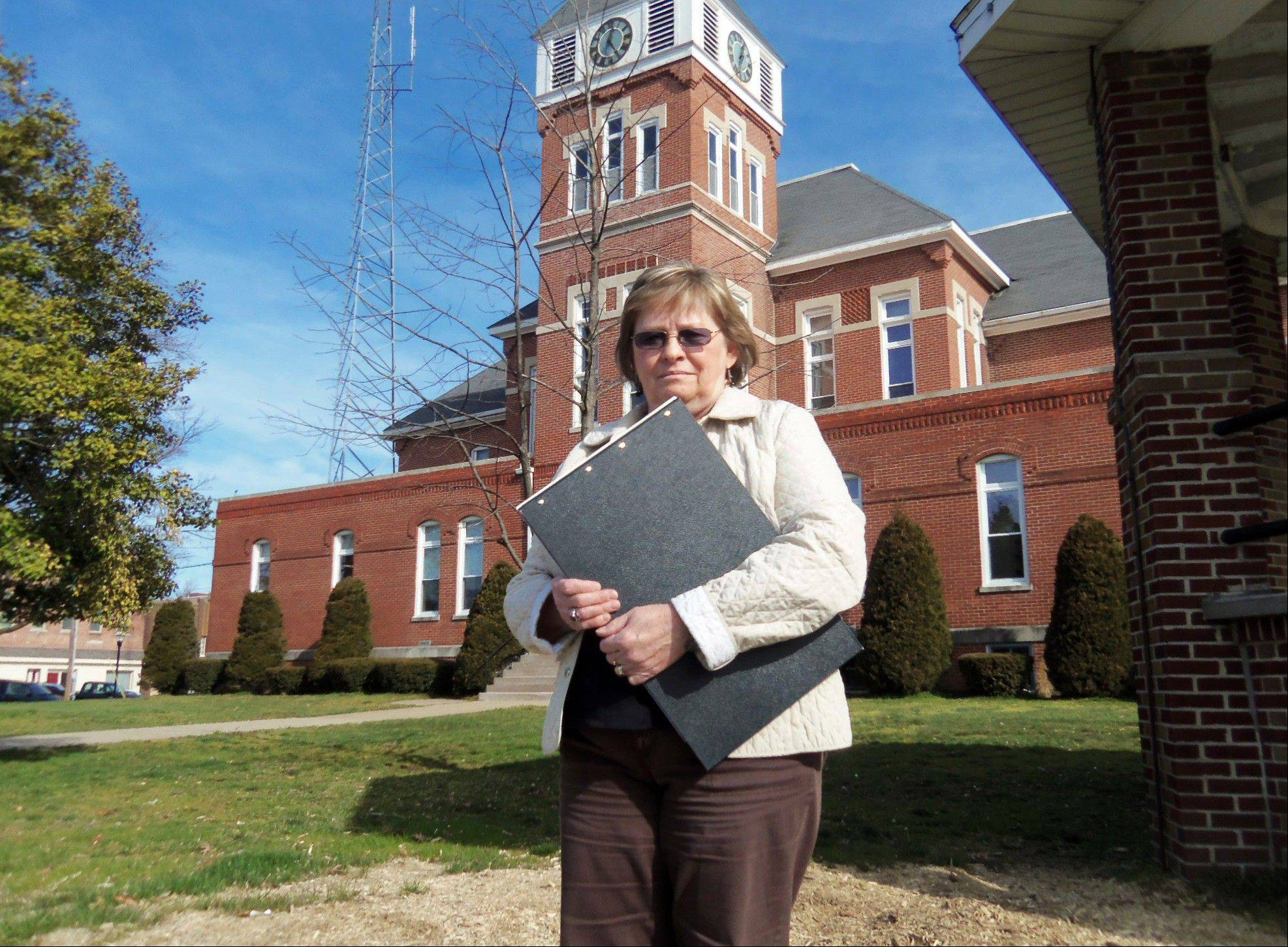 Wayne County Clerk Glenda Young stands outside the Wayne County Courthouse in Fairfield with a book of property records.