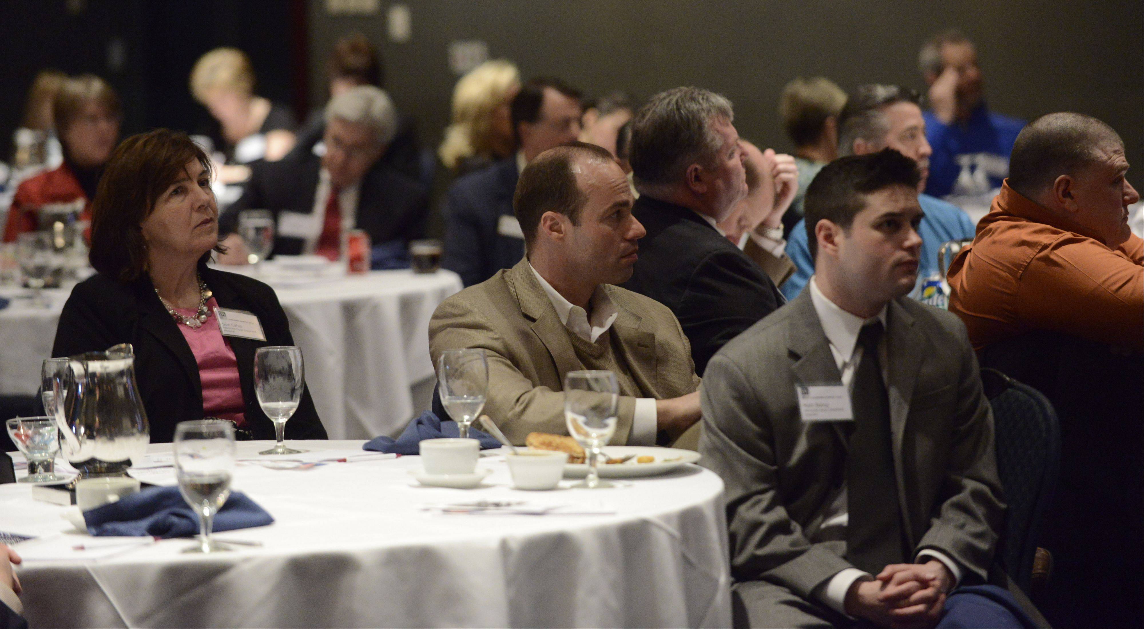 Audience members listen to a presentation during a summit on health care held by the Barrington Area Chamber of Commerce Thursday.