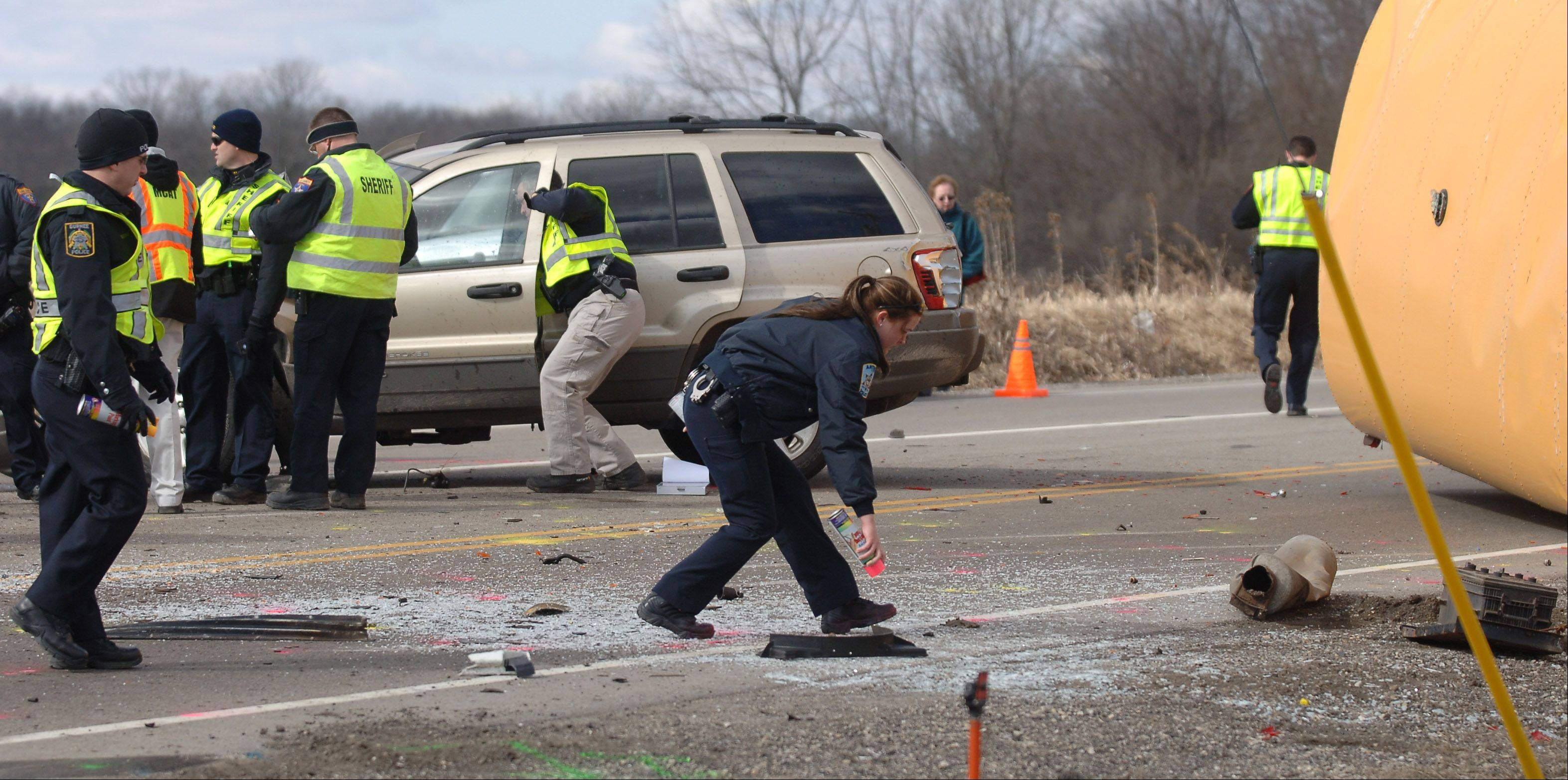 Officials mark the pavement with spray paint at the scene of fatal crash involving two vehicles and a school bus Friday morning at Route 173 and N. Kilbourne Road near Wadsworth.
