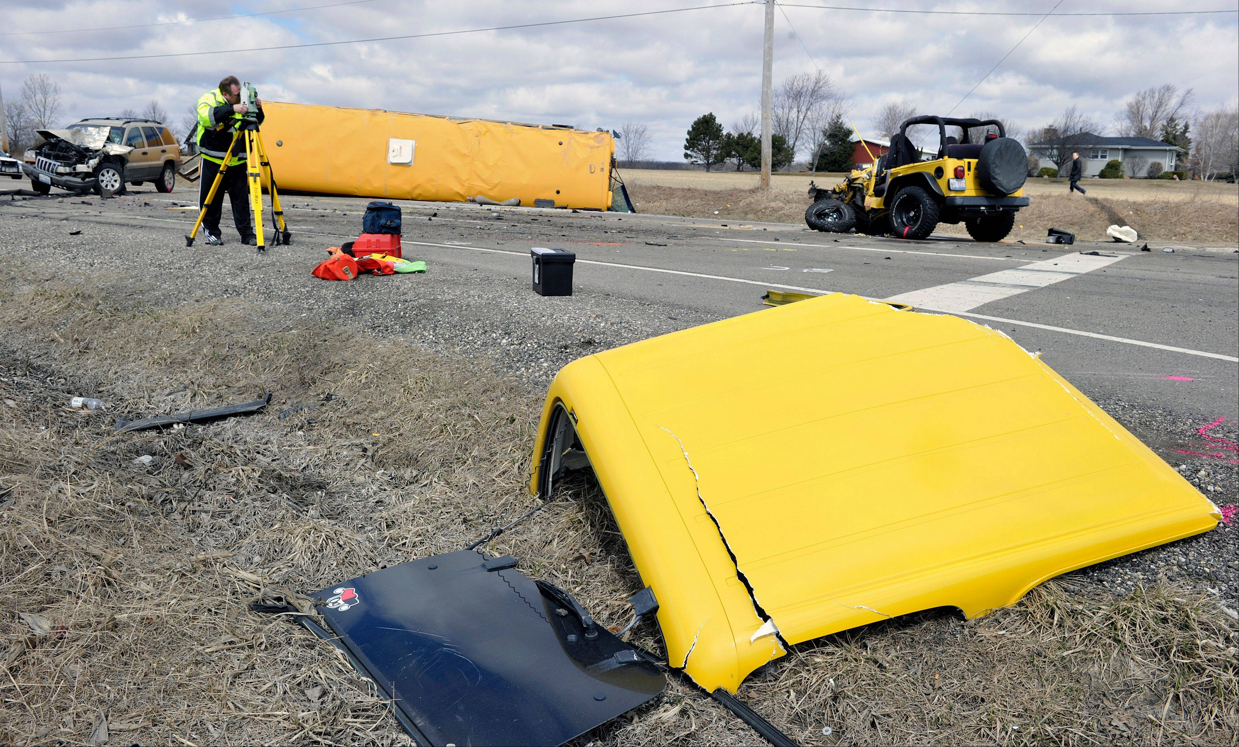 Investigators gather evidence from the scene of a three vehicle accident, including a school bus where the driver of a Jeep Wrangler was killed on Friday, April 5, 2013, near Wadsworth, Ill. Over two dozen schoolchildren were on the bus, most receiving minor injuries.