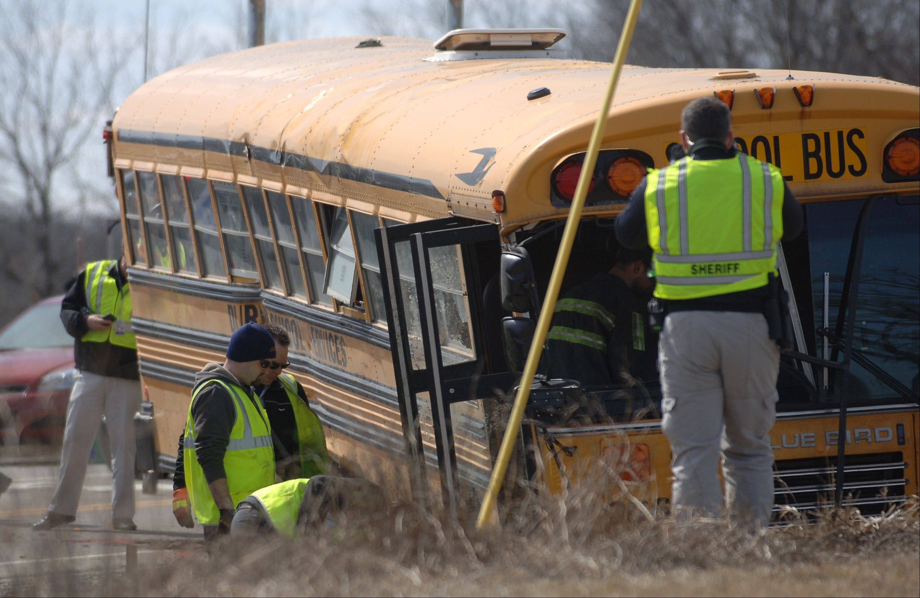 Officials take photos of the bus after it was set back onto its wheels Friday afternoon.