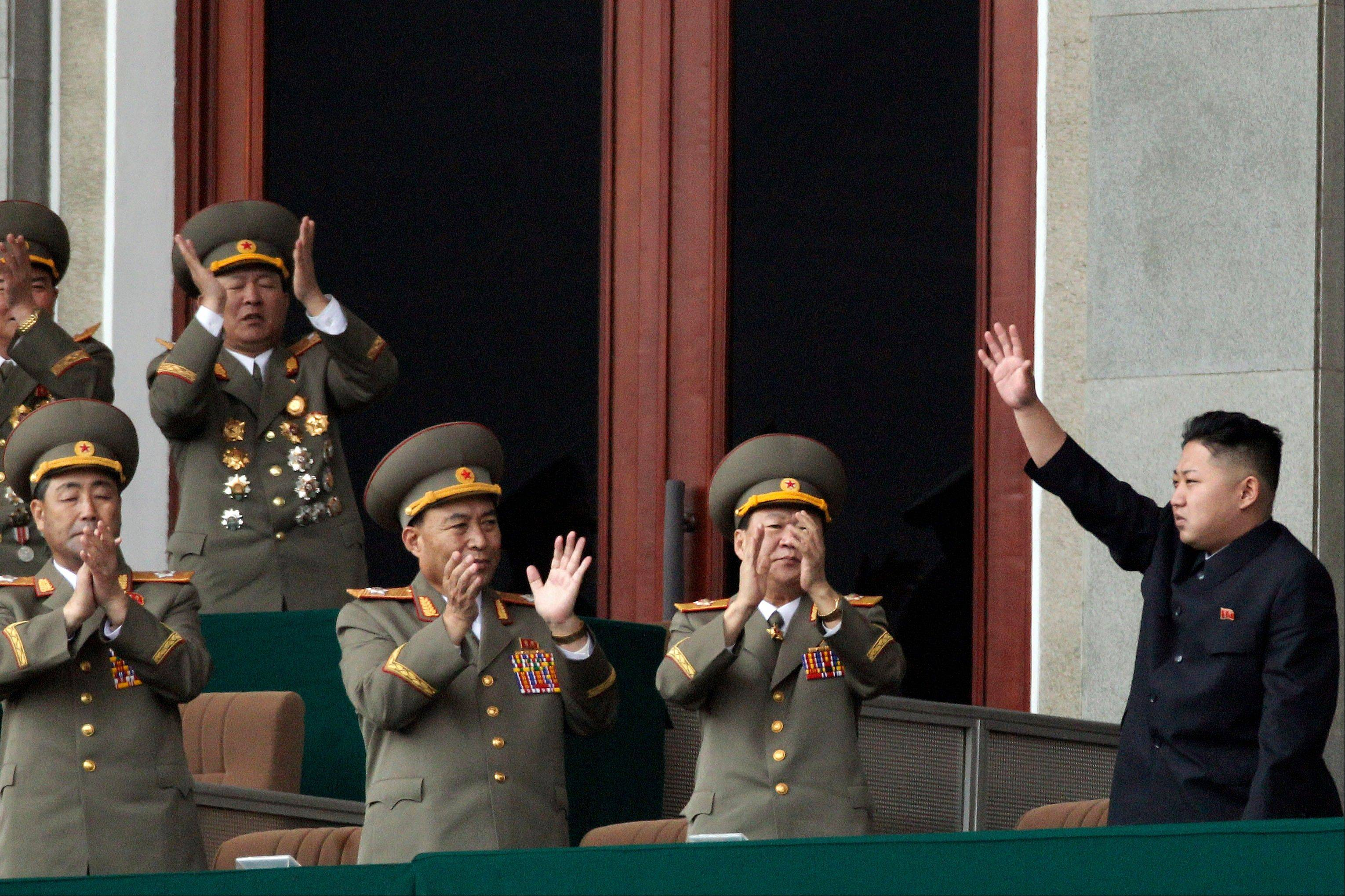 North Korean leader Kim Jong Un, left, waves as North Korean military officers clap at a stadium in Pyongyang during a mass meeting called by the Central Committee of North Korea's ruling party.