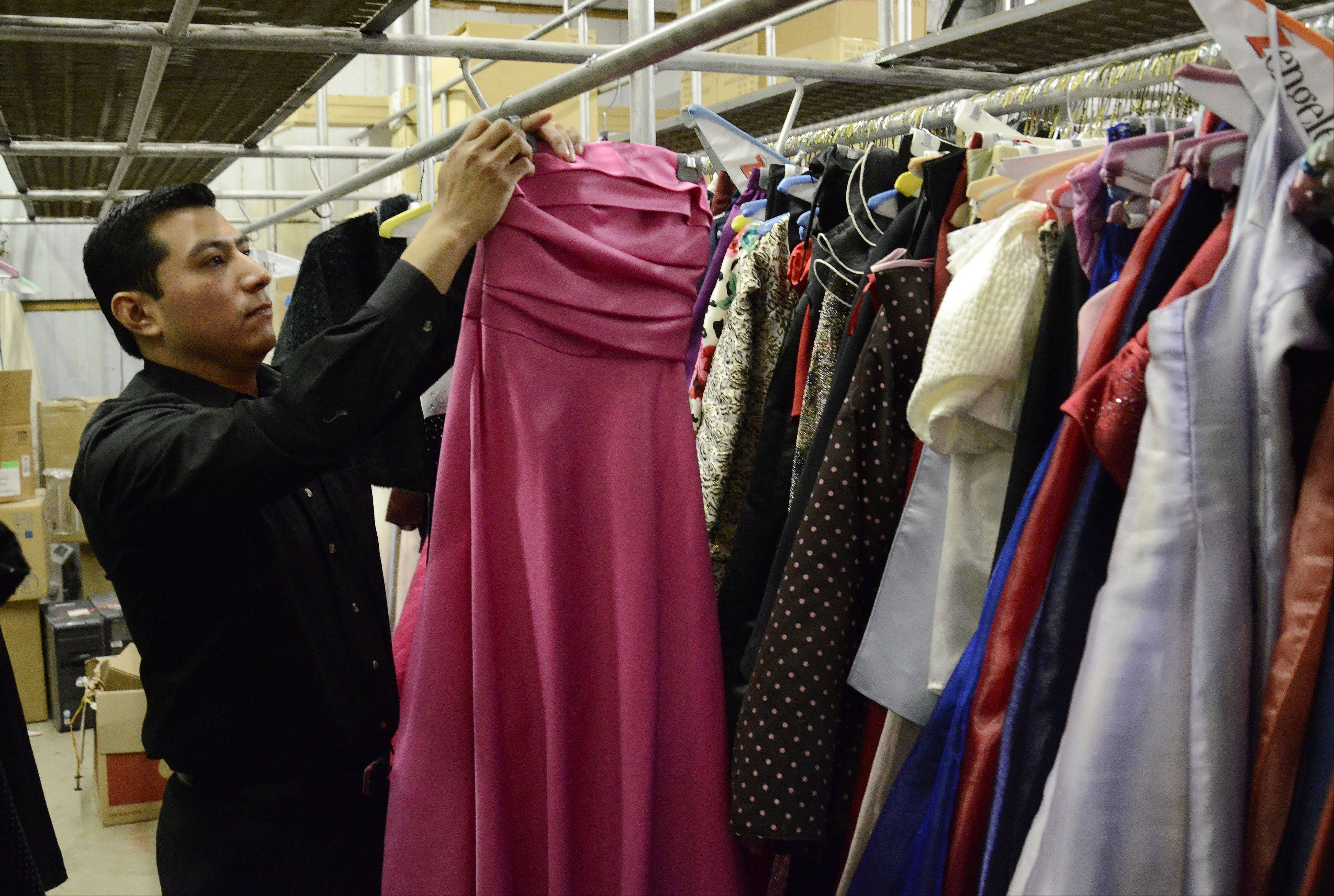"Store manager Oscar Gonzalez sorts through some of the 3,500 new and used prom dresses in the ""vault"" at Zengeler Cleaners in Northbrook, where they are prepared and shipped on behalf of the Glass Slipper Project."