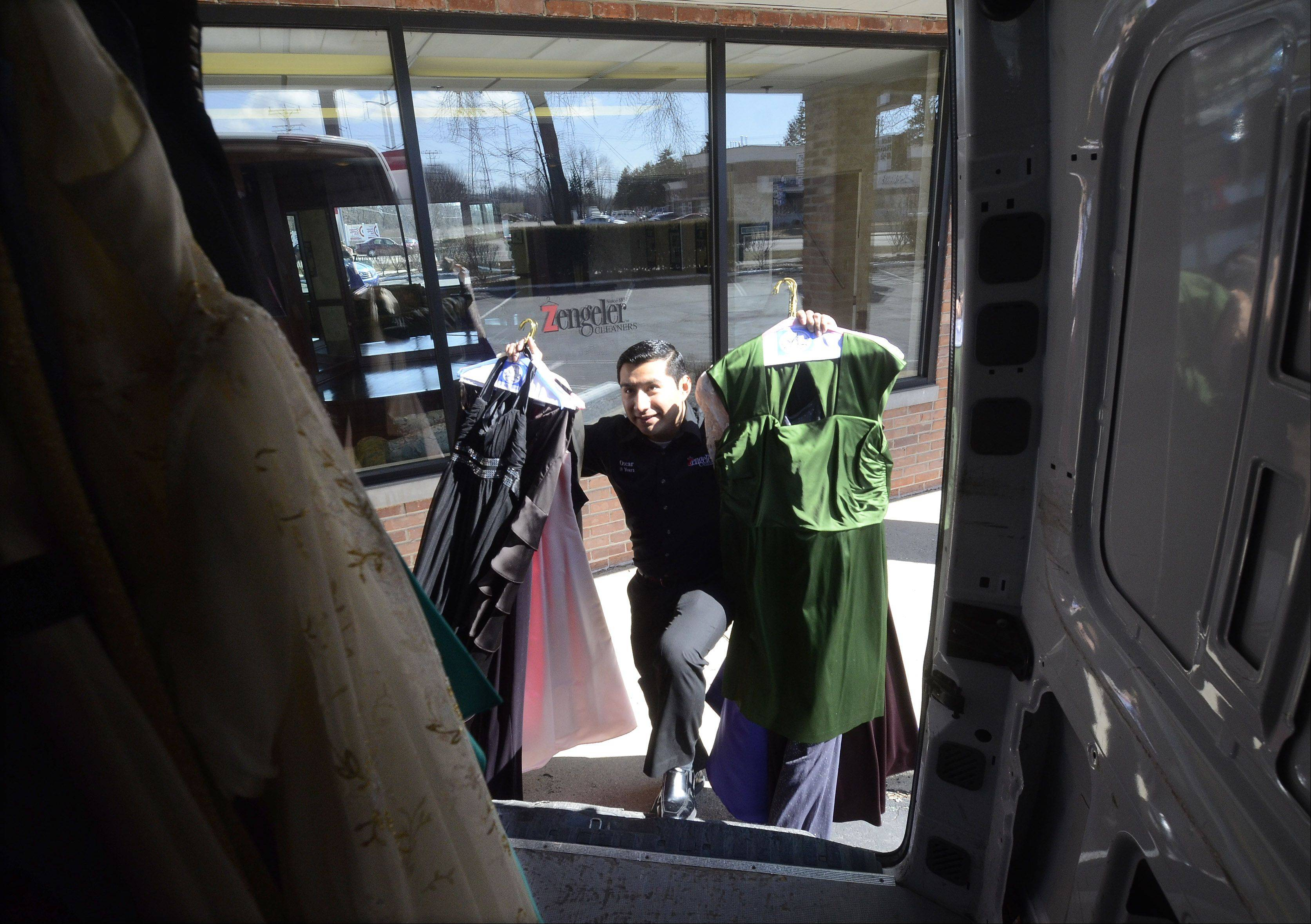 Store manager Oscar Gonzalez of Zengeler Cleaners in Northbrook, loads some of the 3,500 new and used prom dresses donated on behalf of the Glass Slipper Project.