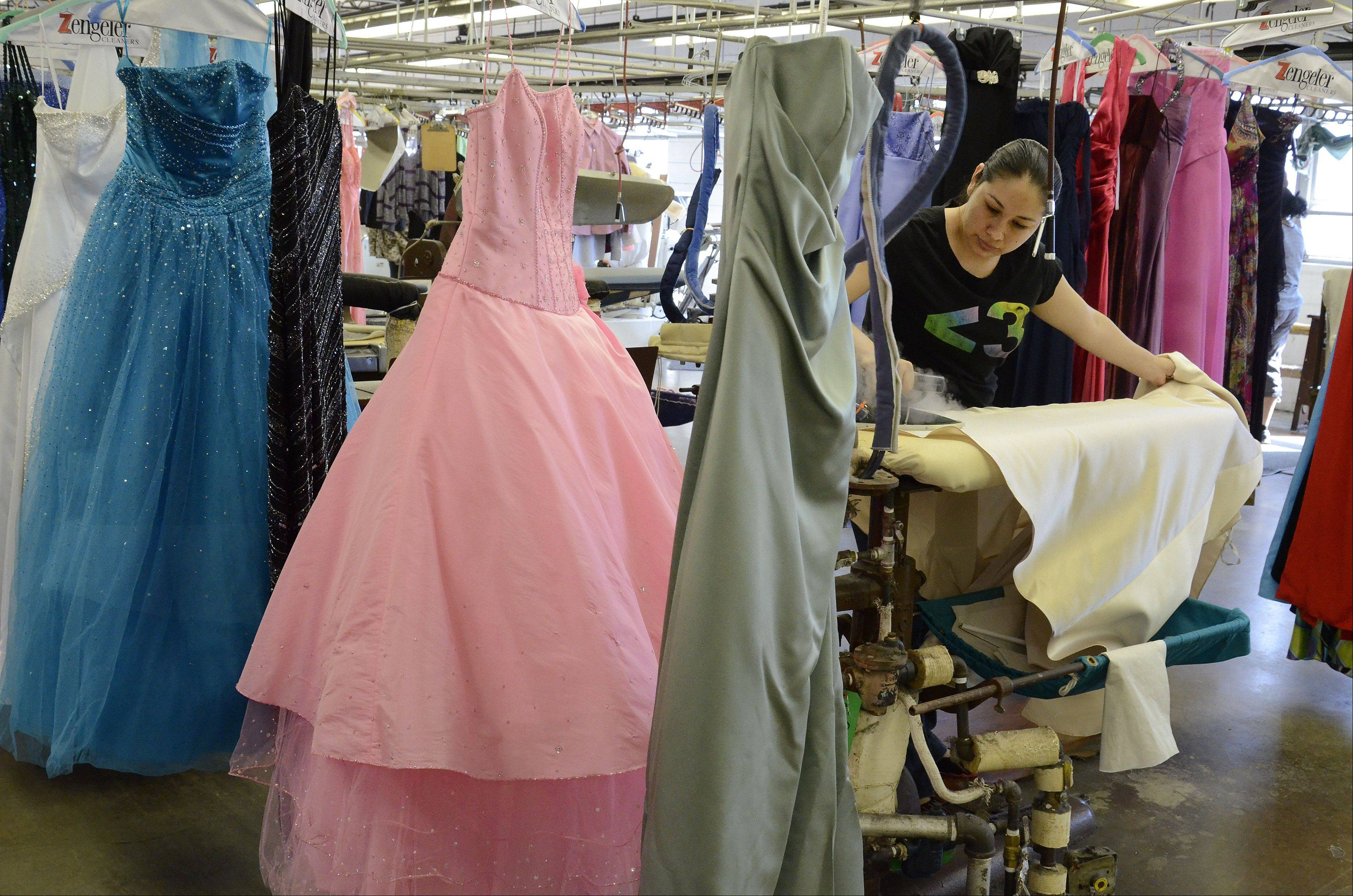 Maria de Jesus of Zengeler Cleaners in Northbrook, presses some of the 3,500 new and used prom dresses donated on behalf of the Glass Slipper Project.