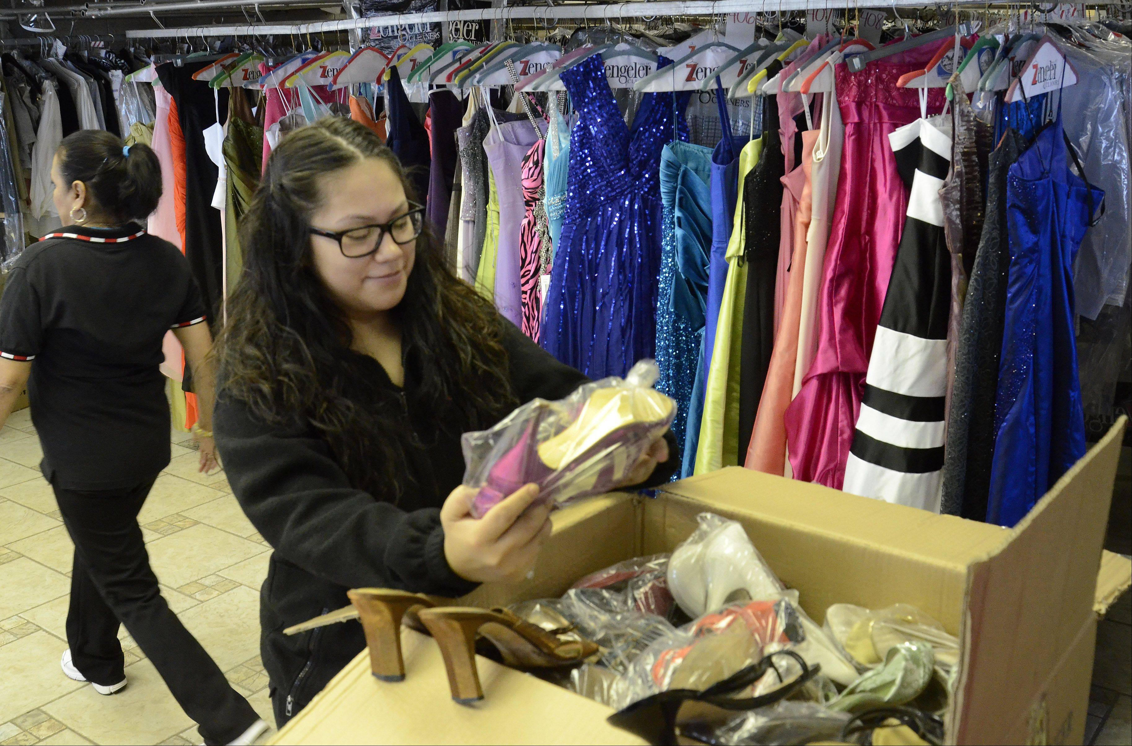 Ana Dominguez sorts through a box of dress shoes at Zengeler Cleaners in Northbrook, where 3,500 new and used prom dresses are prepared and shipped on behalf of the Glass Slipper Project.