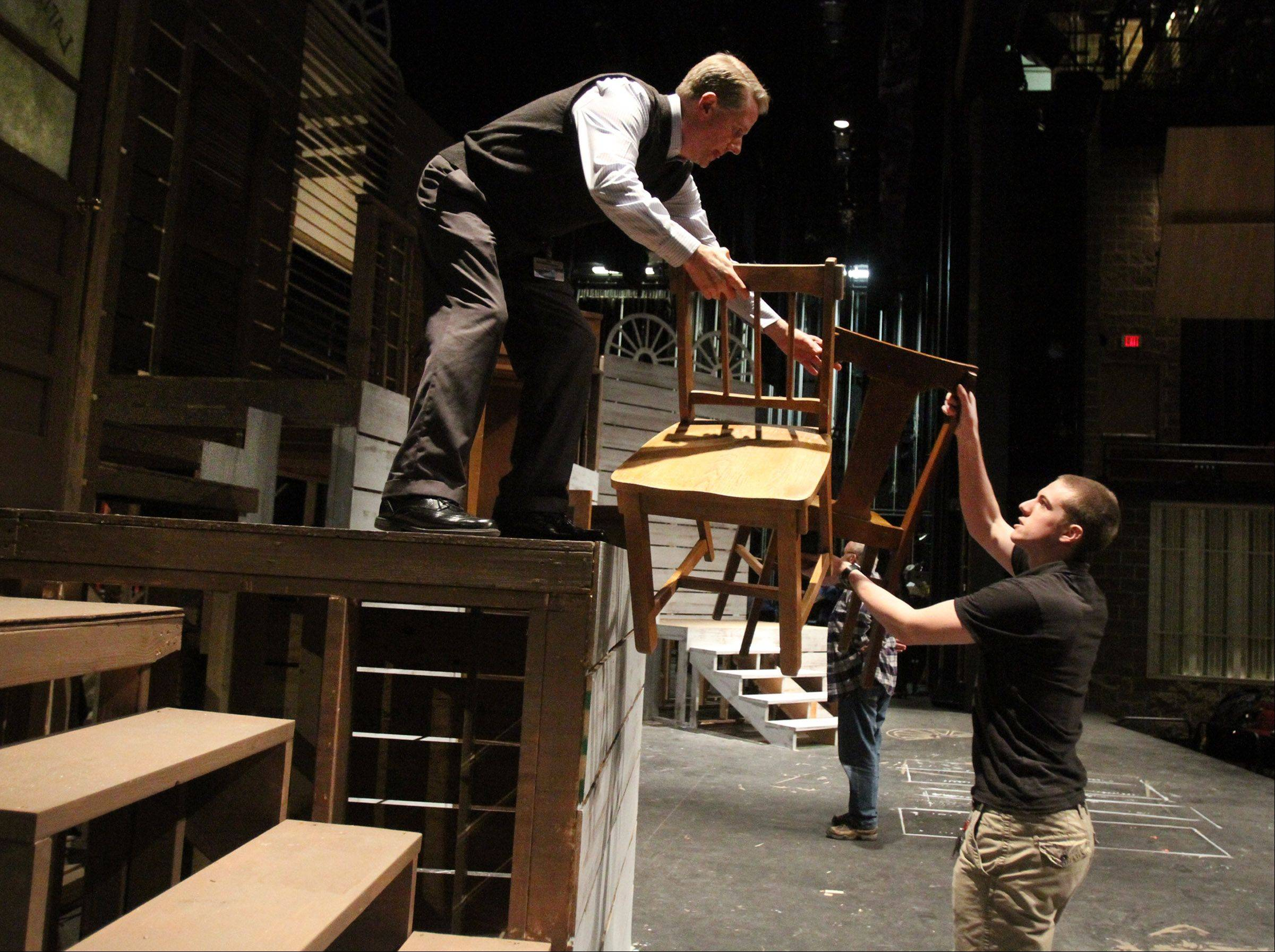 "Long exchanges chairs with Justin Smith, a Harper College Ensemble student, on the set of ""Parade"" in the Performing Arts Center at the college."
