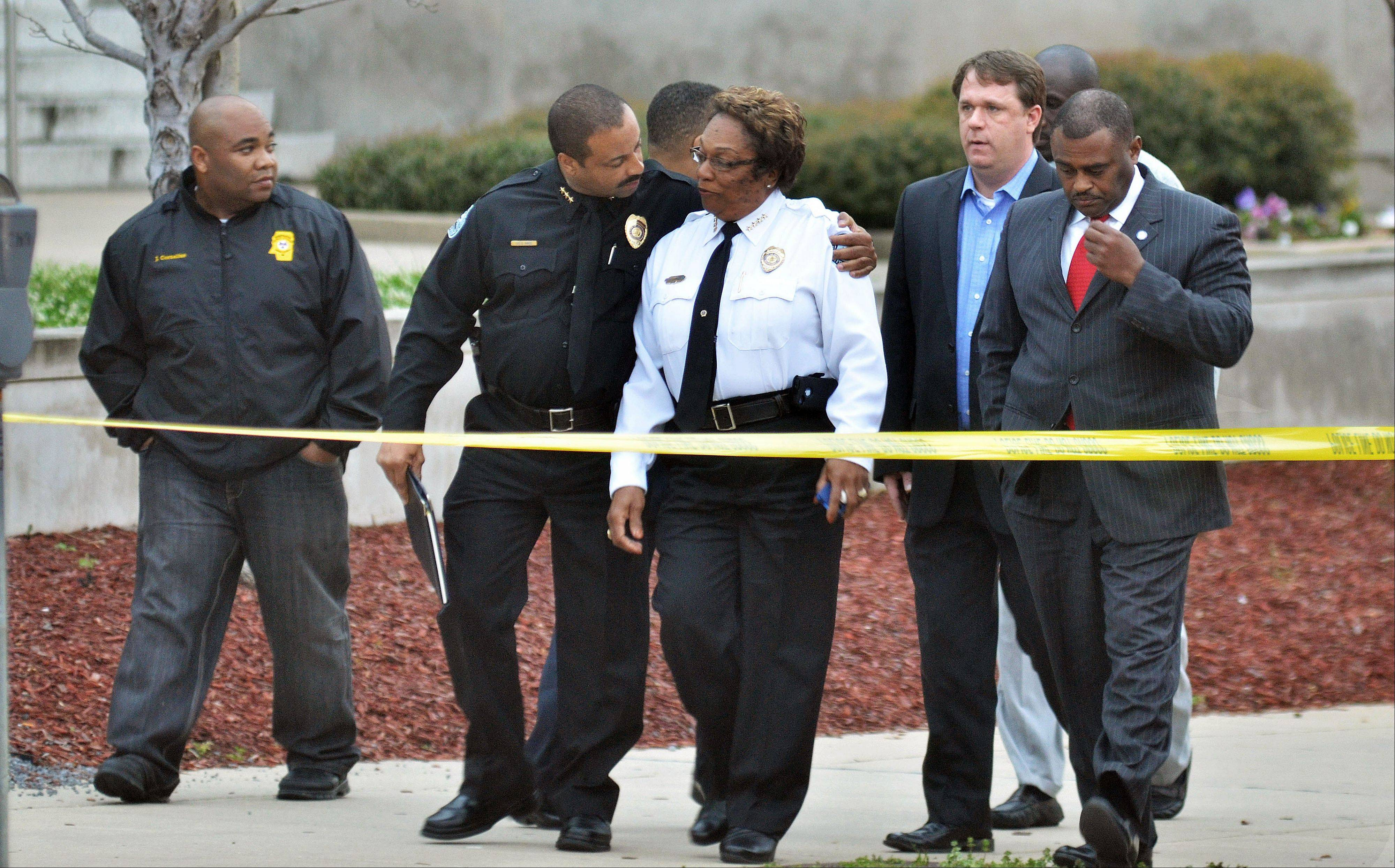 Jackson, Miss. Assistant Chief Lee Vance, center left, comforts Chief Rebecca Coleman, center right, Thursday, April, 4, 2013, after detective Eric Smith was shot and killed inside the Jackson Police Department. A suspect was also killed.