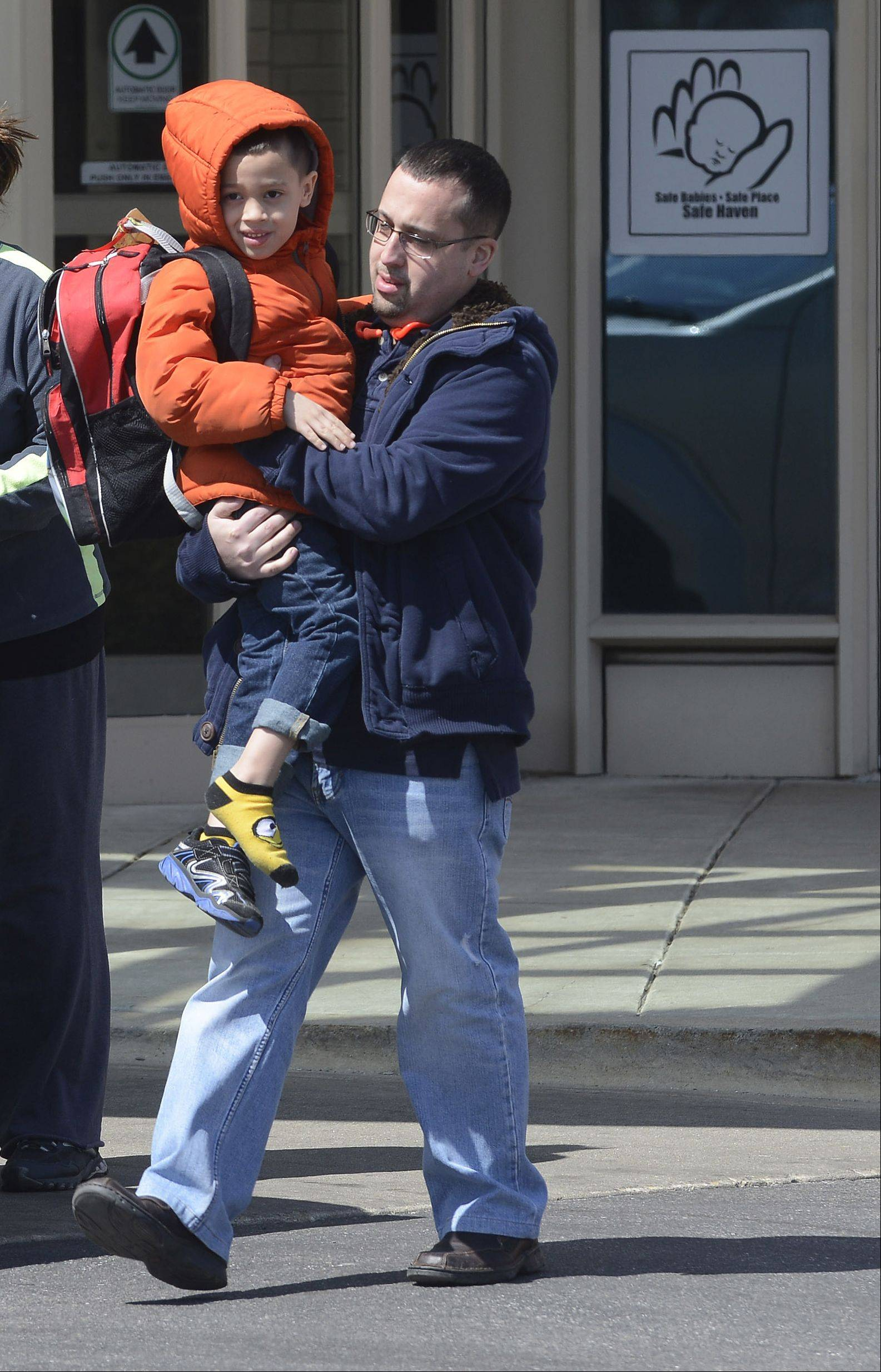 "A father carries his son, who was a passenger on the bus in Friday's crash near Wadsworth, to a waiting car after the family was reunited at Advocate Condell Medical Center in Libertyville. ""He's fine. He lost a shoe,"" Dad said."