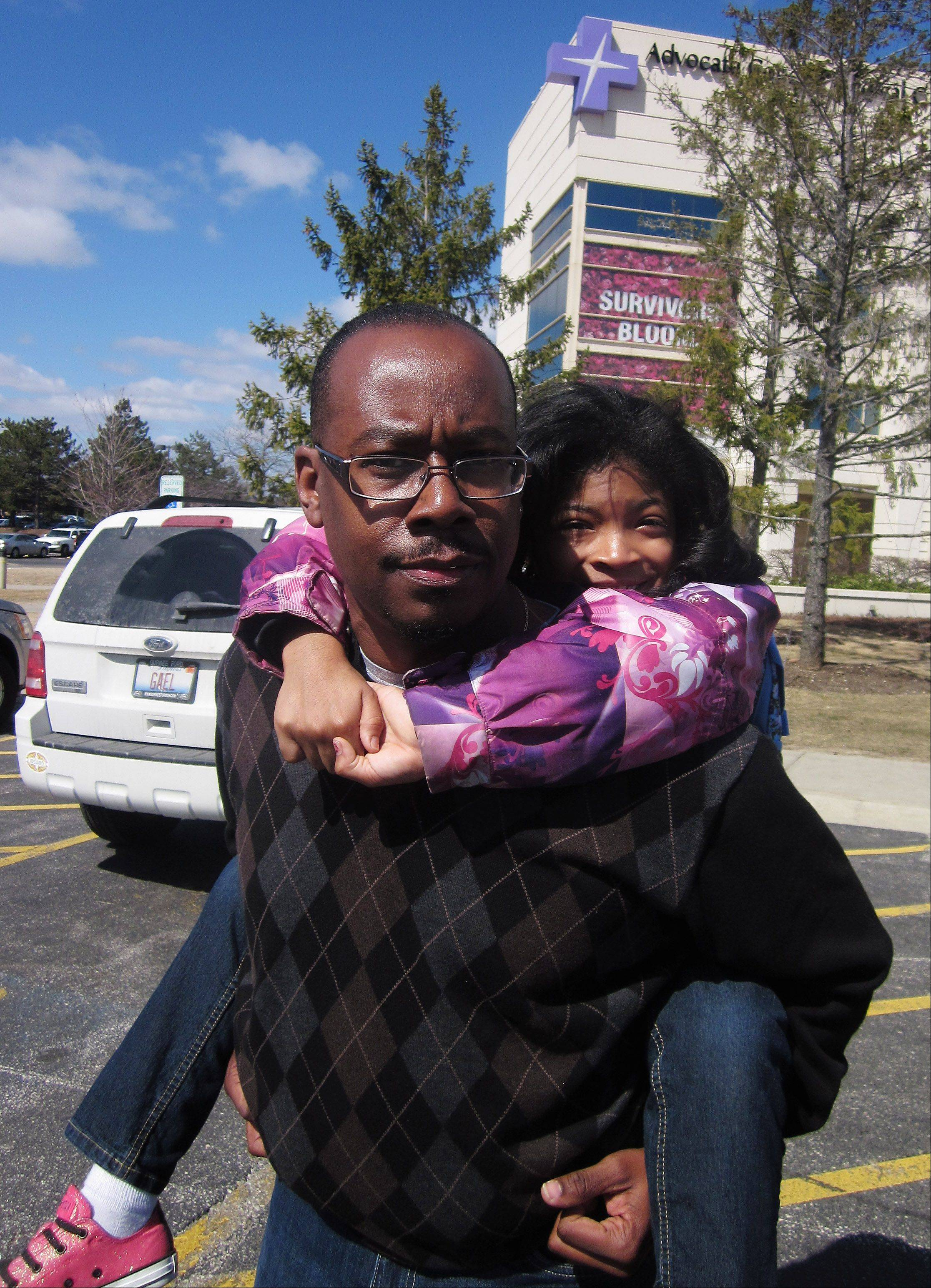 Cliff Smith of Zion carries his daughter Mariah, 8, after they were reunited at Advocate Condell Medical Center in Libertyville. She was a passenger on the school bus involved in a crash near Wadsworth.