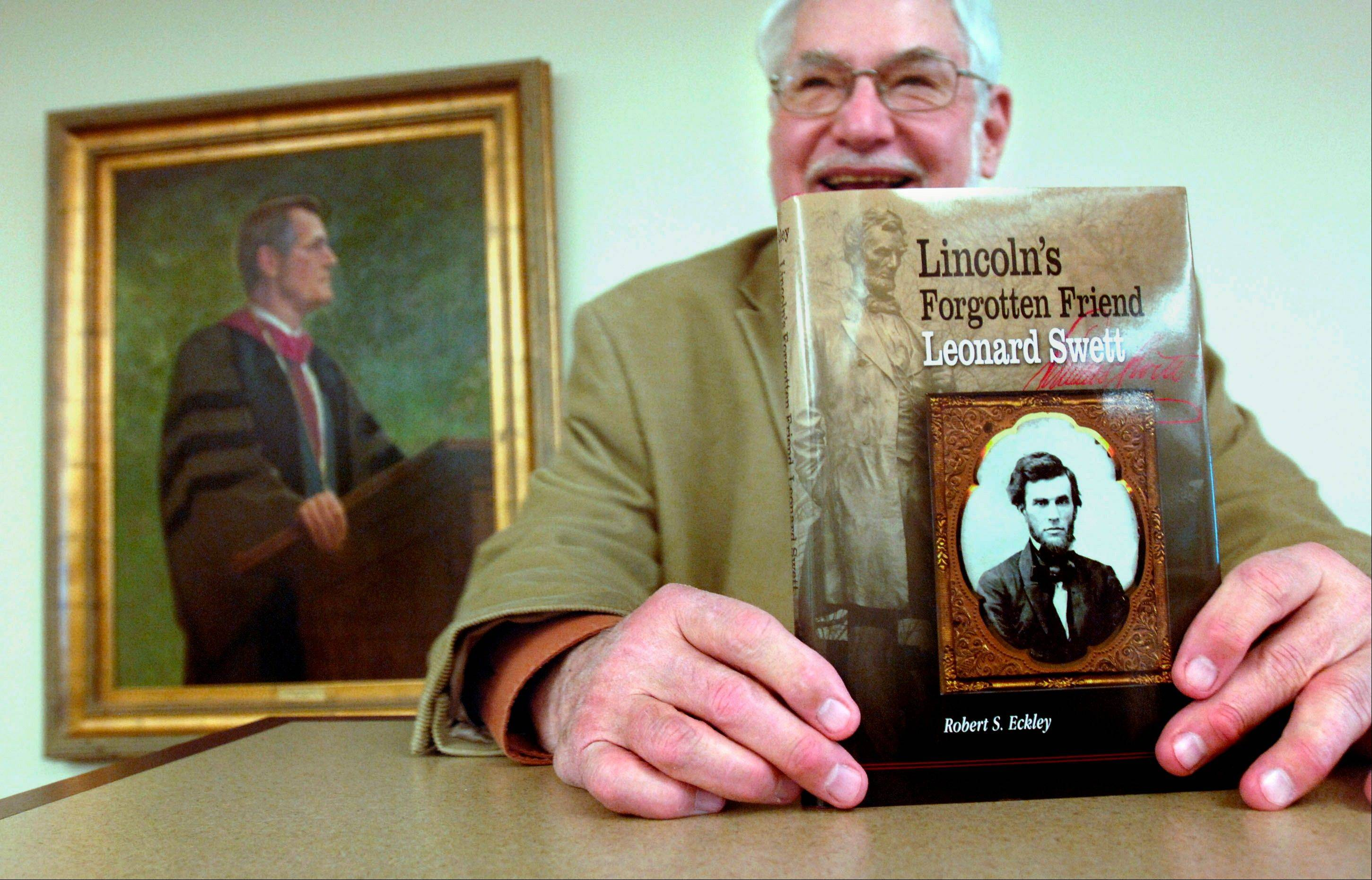 "Associated PressProf. Robert Bray holds a copy of Robert S. Eckley's ""Lincoln's Forgotten Friend, Leonard Swett,"" at Illinois Wesleyan University's Ames Library in Bloomington. A portrait of Eckley, a former president of IWU, is at left."