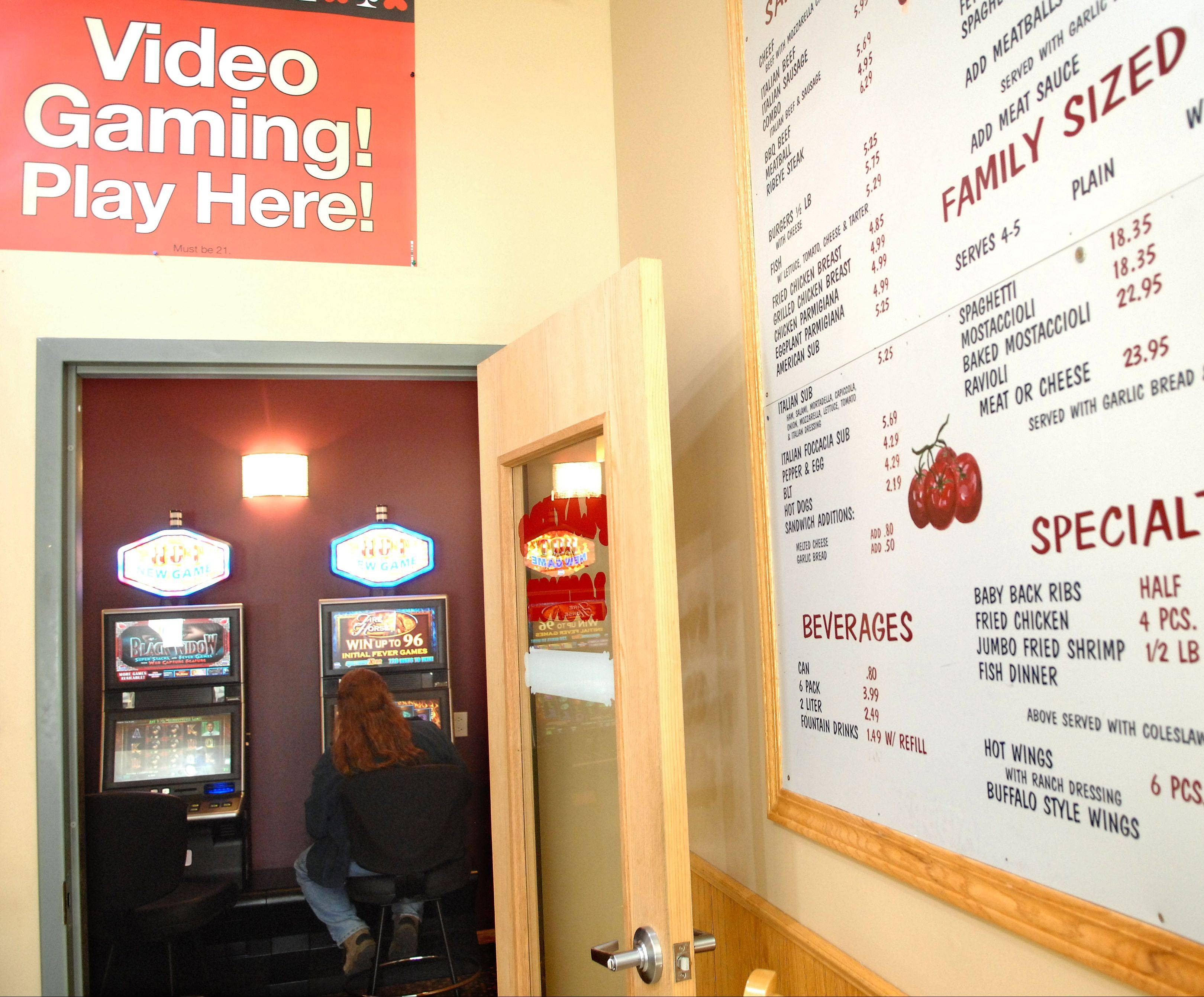 A lunchtime customer plays a video gambling machine at Rosati's in Lakemoor. Money from the machines is helping to ease the business's financial struggles, the owner says.