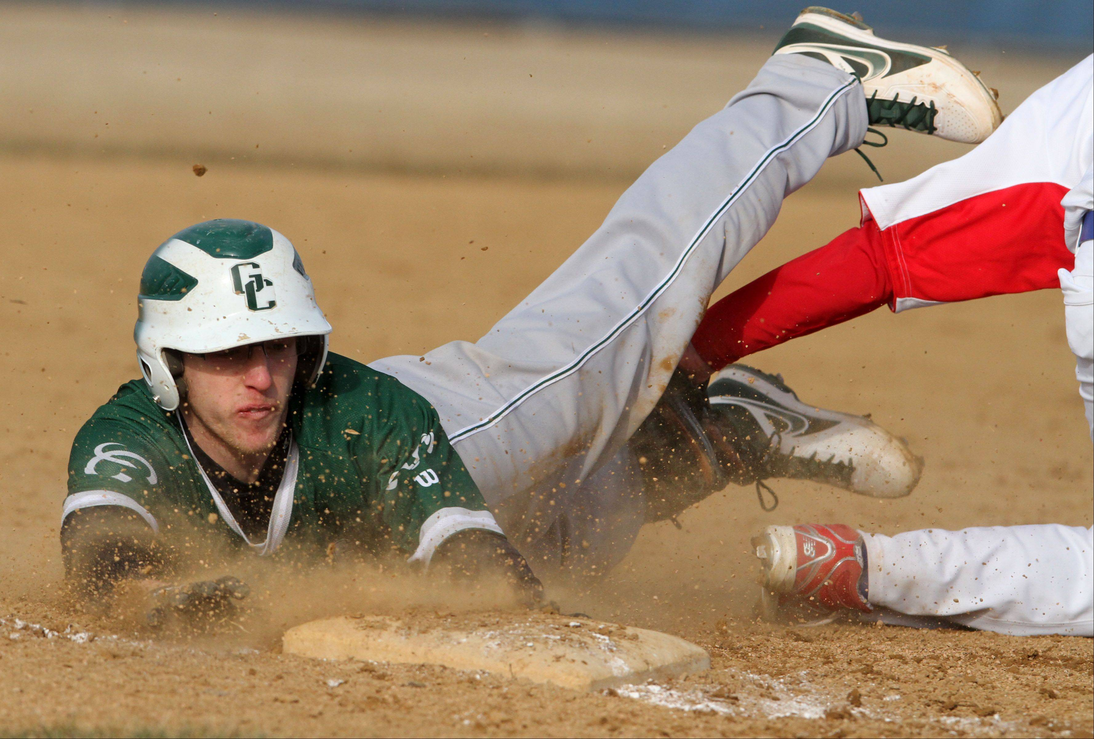 Grayslake Central's Danny Reed is called safe sliding head first into third base as Lakes' Nick Seketa attempts to apply the tag at Lakes on Friday.