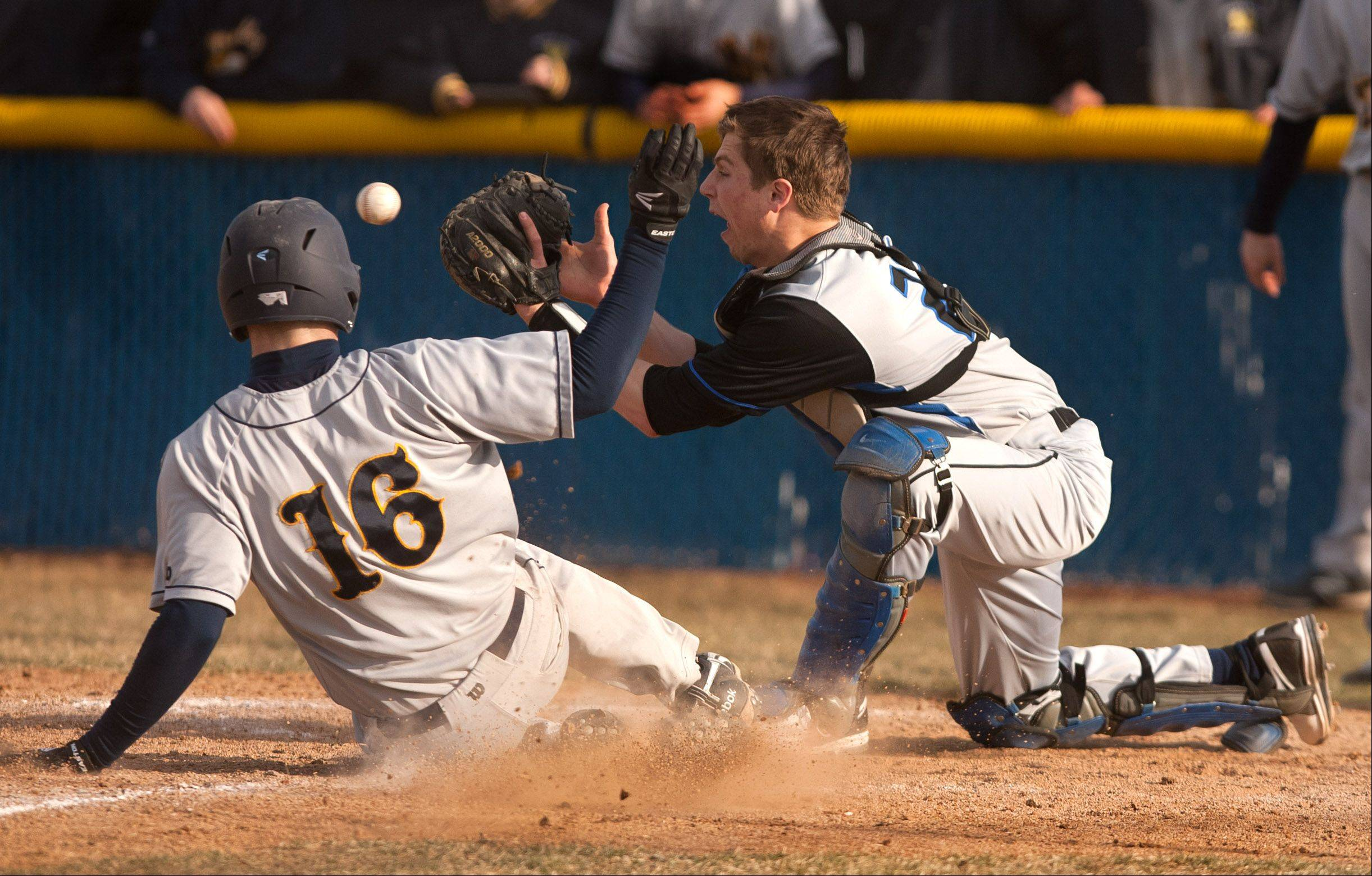 Neuqua Valley's Jeff Evak slides safely into home as the ball is late getting to St. Charles North catcher Ryan Thomas, during boys baseball action in Naperville.