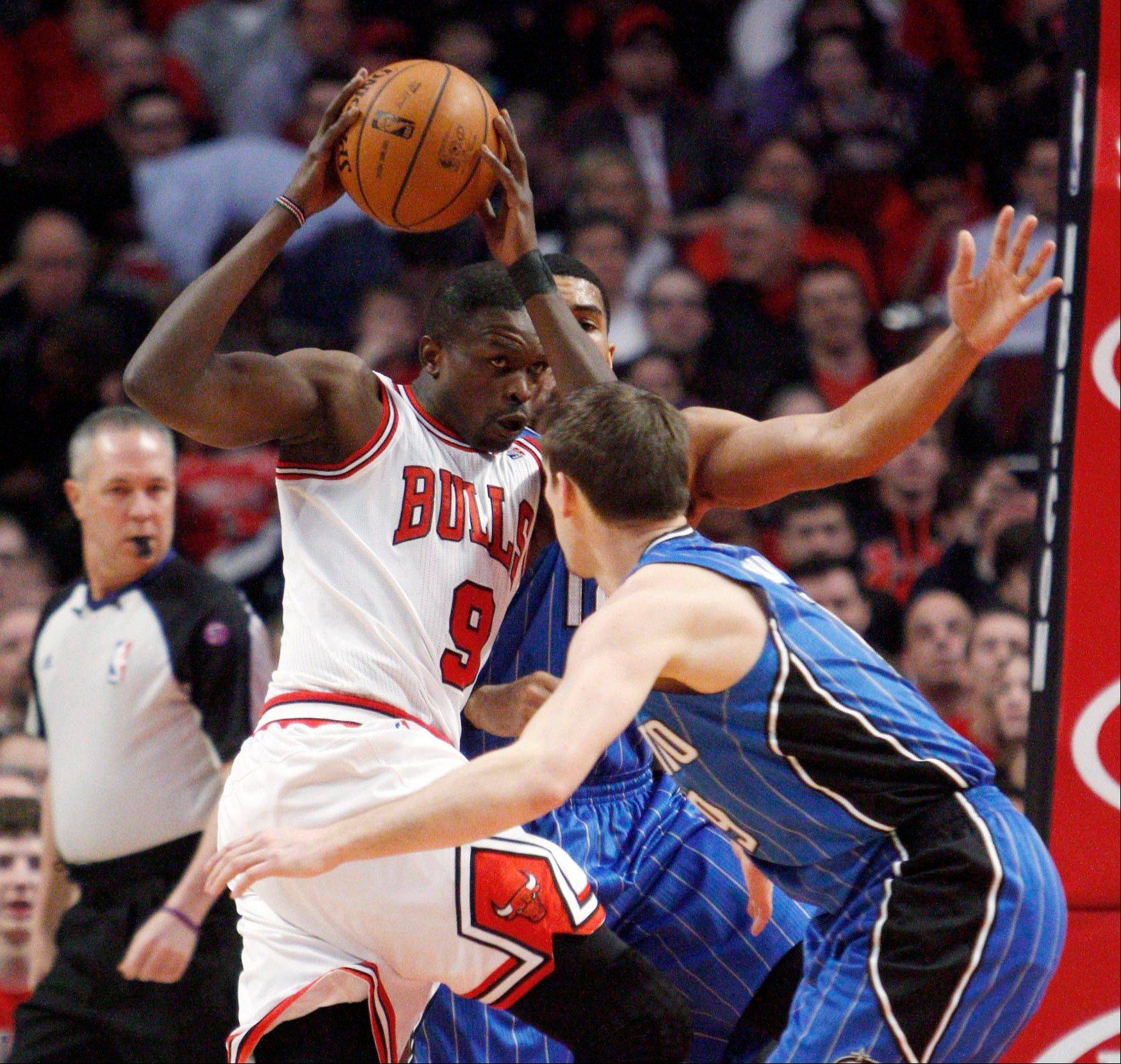 Chicago Bulls' Luol Deng drives between Orlando Magic's Beno Udrih, front, and Tobias Harris during the first half of an NBA basketball game Friday, April 5, 2013, in Chicago.