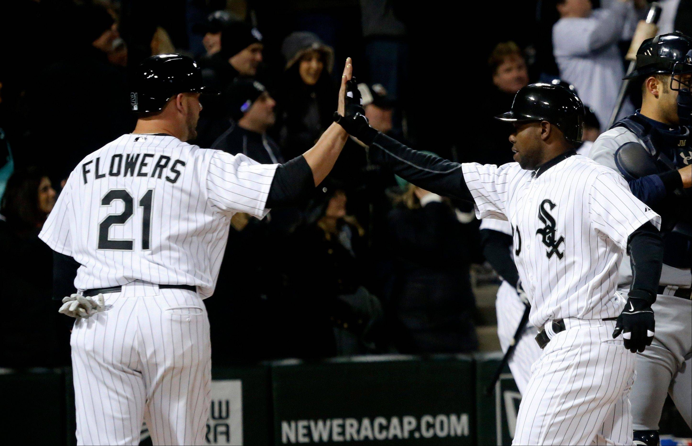 Tyler Flowers (21) greets teammate Alejandro De Aza at home after they both scored on De Aza's home run off Seattle Mariners starting pitcher Blake Beavan during the fifth inning of a baseball game on Friday, April 5, 2013, in Chicago.