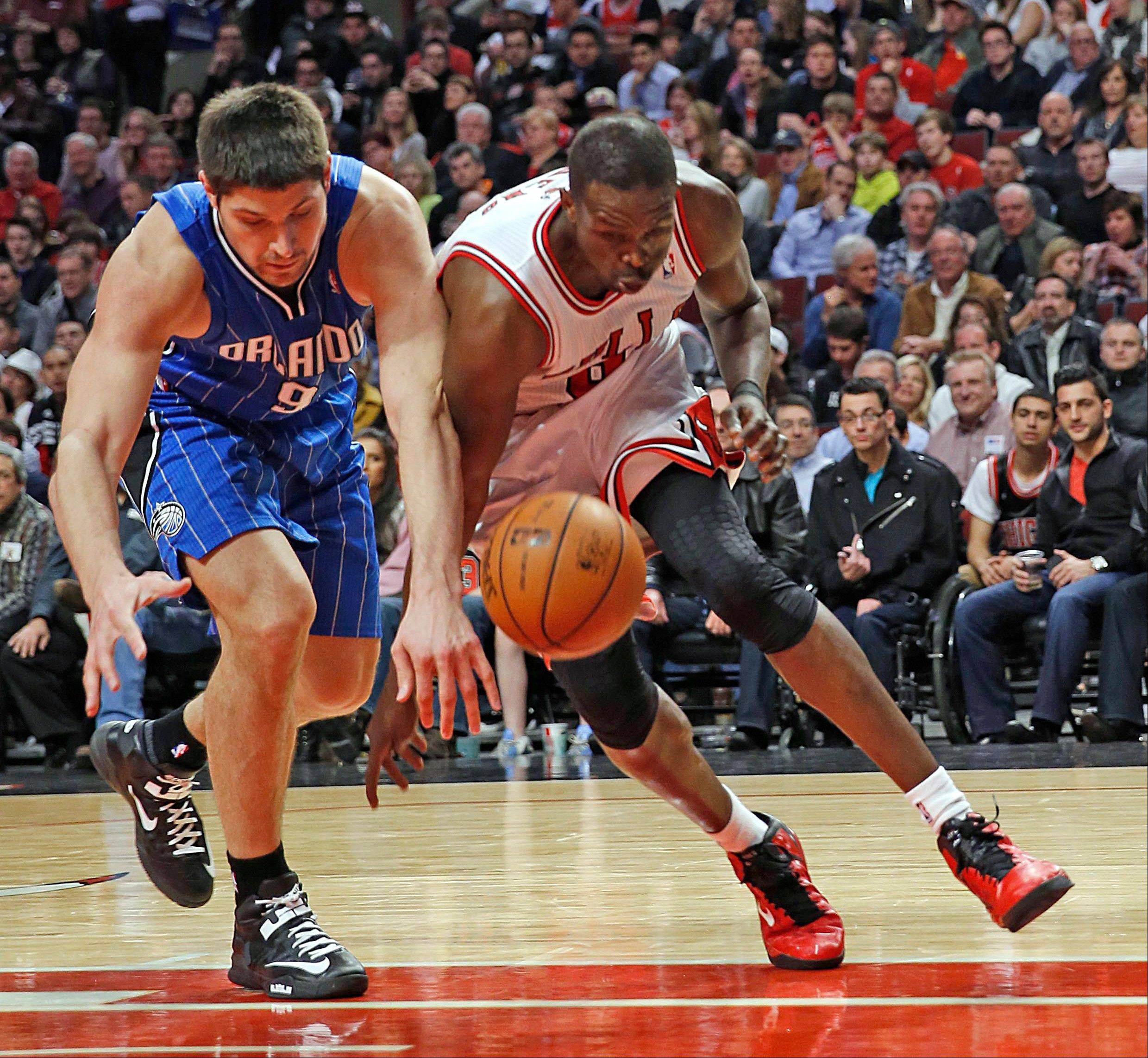 Luol Deng and Orlando Magic's Nikola Vucevic vie for a loose ball during the fourth quarter as the Bulls beat the Magic 87-86 in an NBA basketball game on Friday, April 5, 2013 in Chicago.