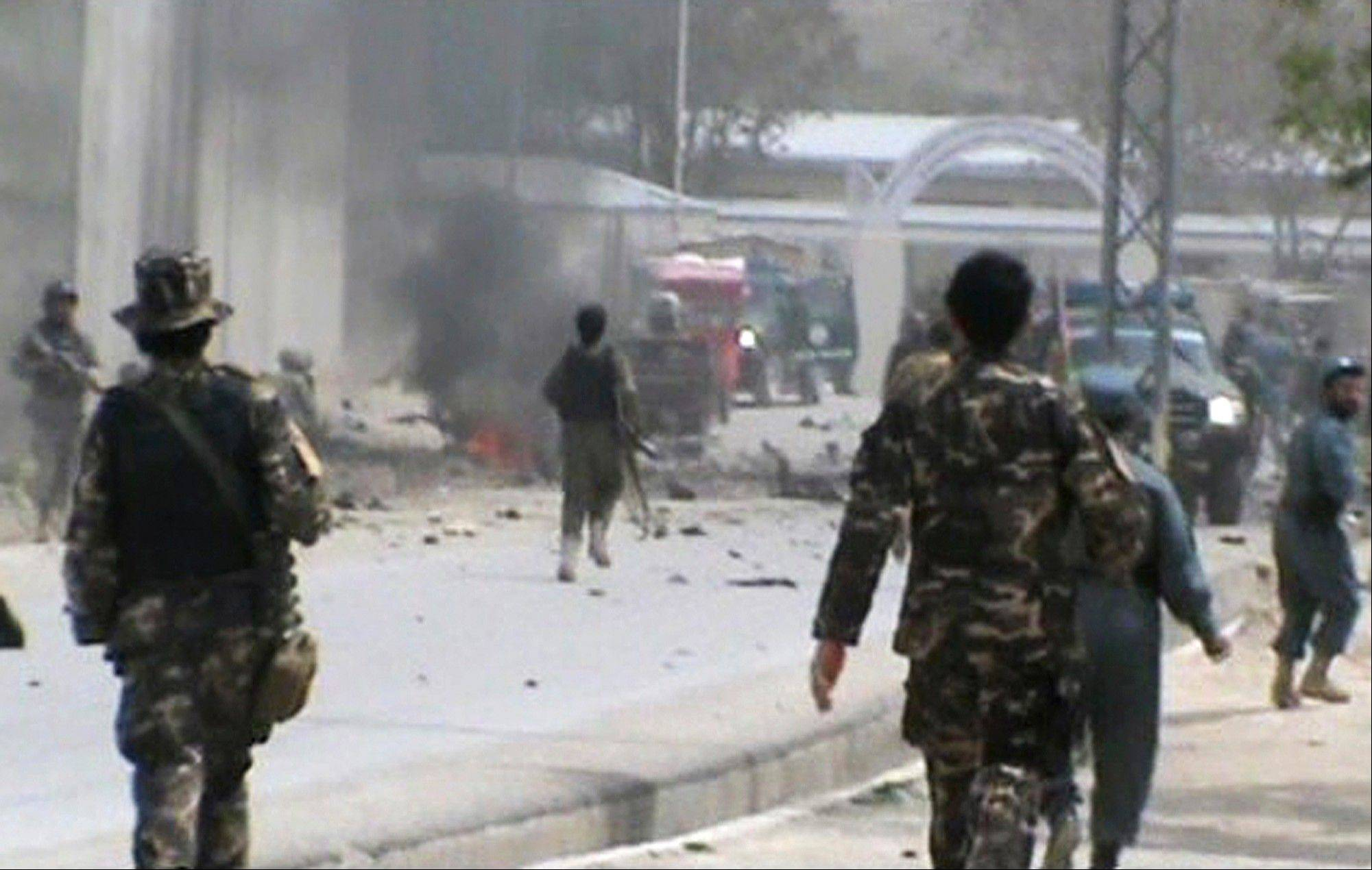 This image made from AP video shows Afghan National Army soldiers rushing to the scene moments after a car bomb exploded in front the PRT, Provincial Reconstruction Team, in Qalat, Zabul province, southern Afghanistan, Saturday, April 6, 2013. Three U.S. soldiers, two U.S. civilians and a doctor were killed when a suicide bomber detonated a car full of explosives just as a convoy with the international military coalition drove past another convoy of vehicles carrying the governor of Zabul province.