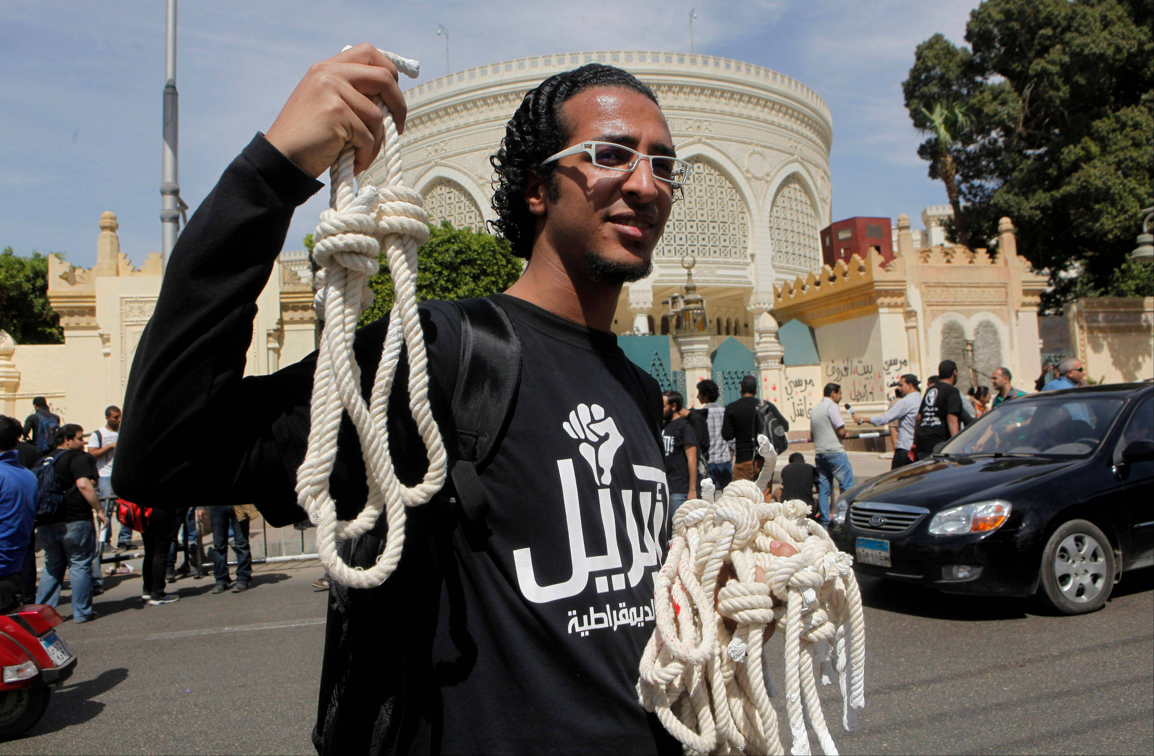Associated Press A member of Egypt�s April 6 Youth Movement distributes nooses in front of the presidential palace in Cairo Saturday, April 6. The group is rallying to mark its fifth anniversary and to protest against President Mohammed Morsi.