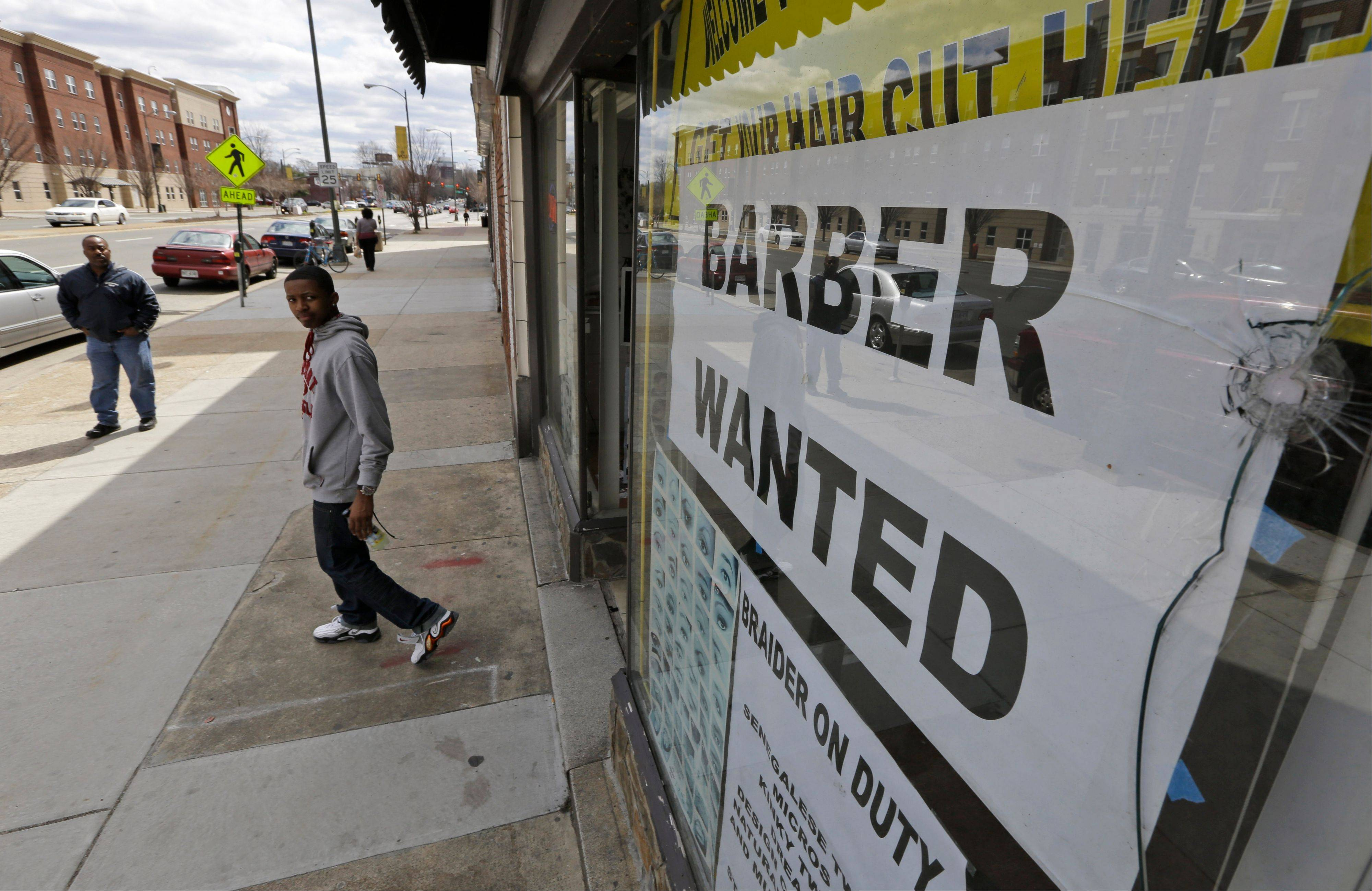 This March 29 photo shows a help wanted sign at a barber shop in Richmond, Va. U.S. employers added just 88,000 jobs in March, the fewest in nine months and a sharp retreat after a period of strong hiring. Many discouraged Americans are giving up the job hunt for school, retirement and disability.
