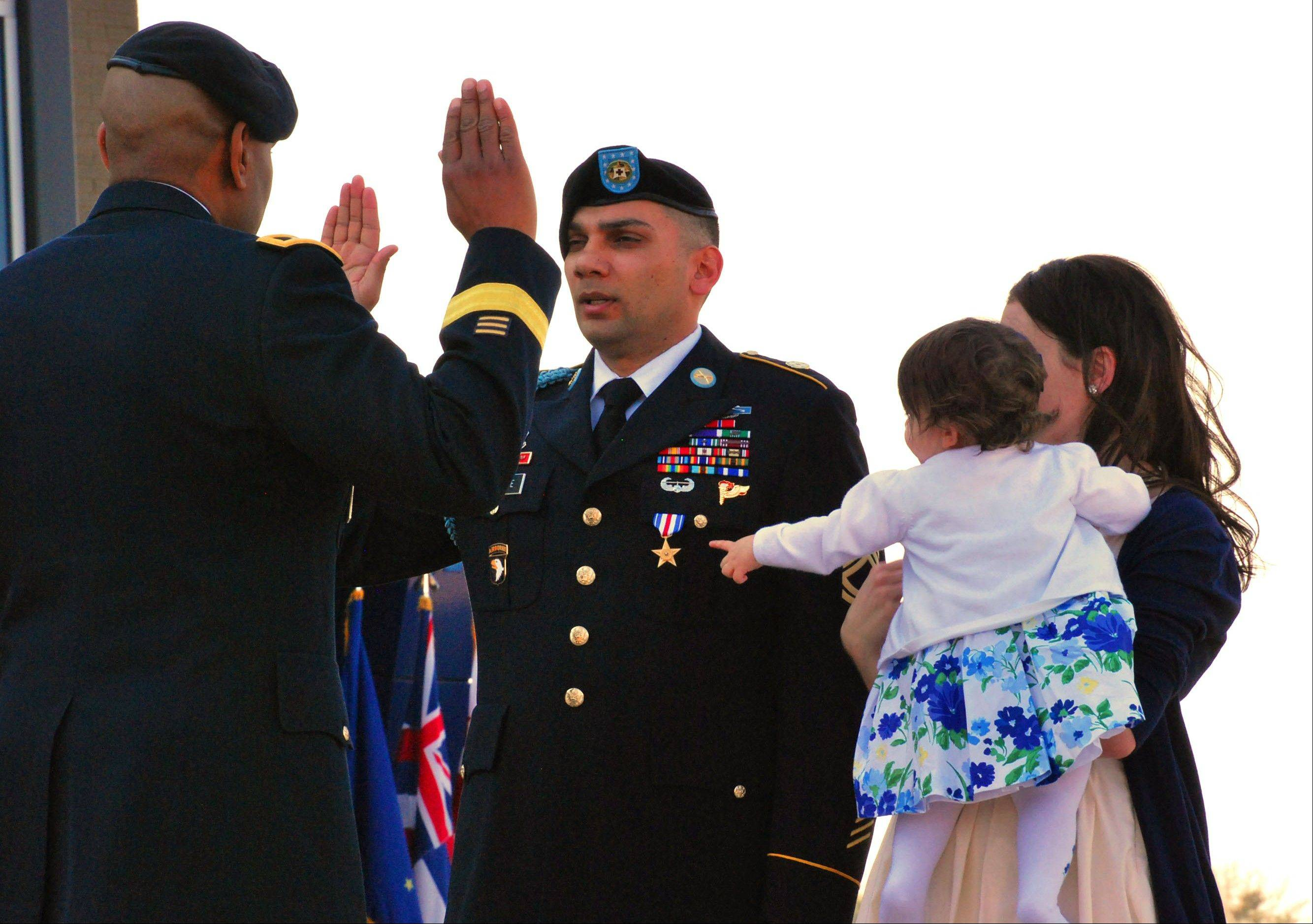 Sgt. 1st Class Matthew Loheide re-enlists in the Army on Friday, April 5, at Fort Campbell, Ky., while his daughter, Annabella, held by Marianne Loheide, points to his Silver Star. Loheide received the Silver Star for his actions to evacuate wounded soldiers while in Afghanistan in 2010.