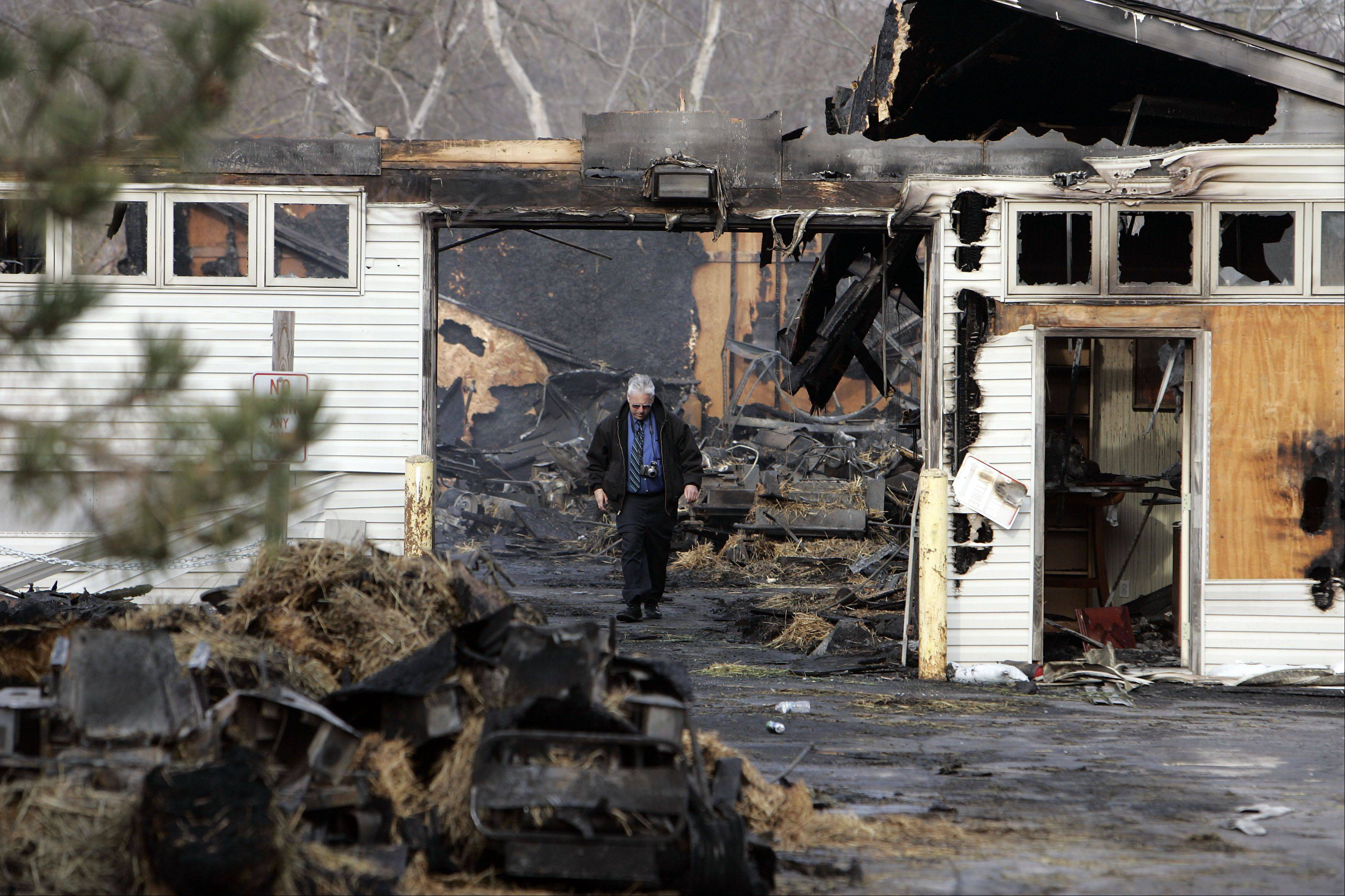 An unidentified man walks through what is left of a warehouse of Trinity Landscape of Northern Illinois, where its owner, Kurt Cina, died in a fire Friday evening.