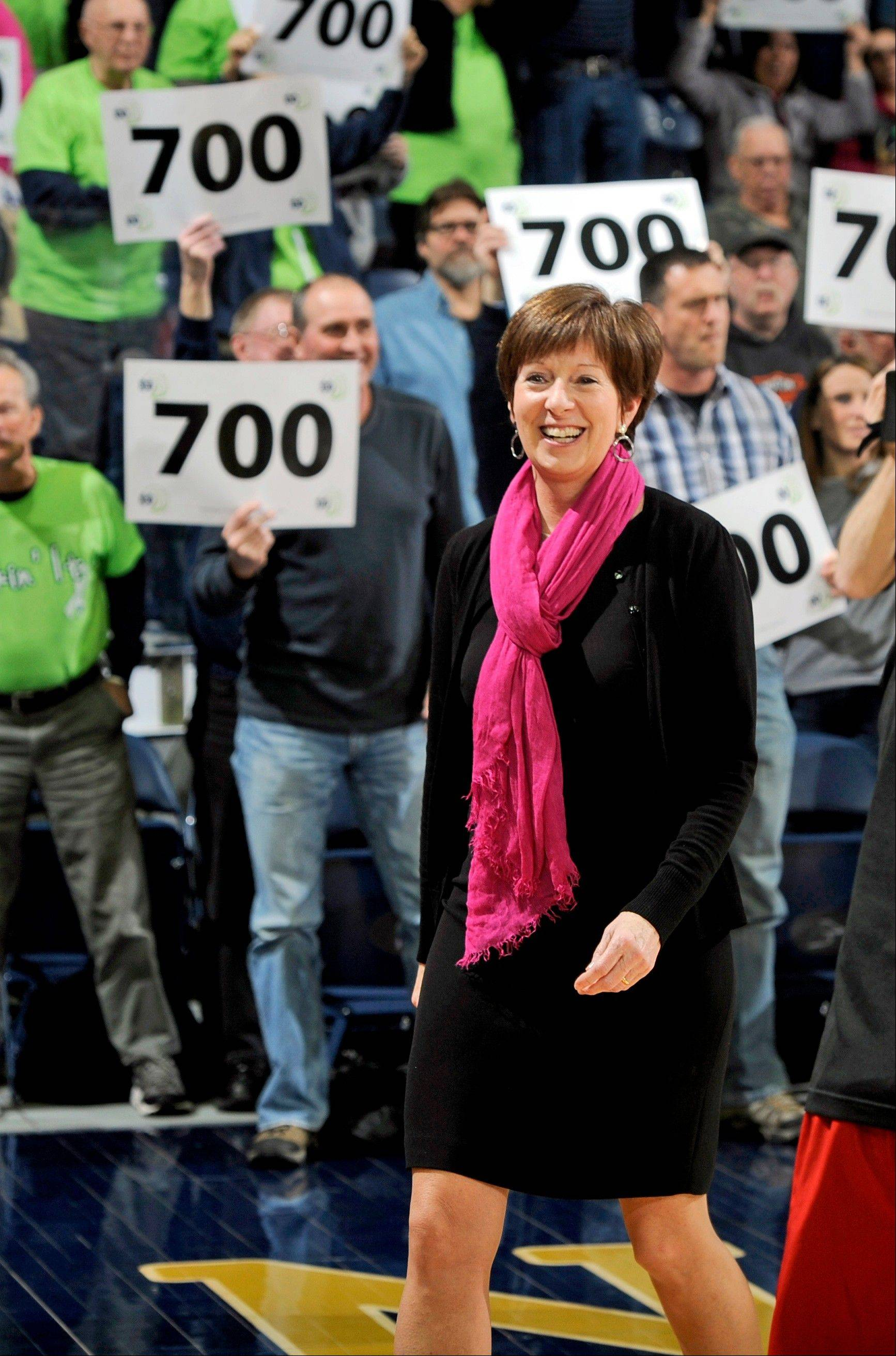 FILE - In this Feb. 11, 2013, file photo, Notre Dame head coach Muffet McGraw reacts to the crowd holding up signs with 700 on them in honor of her 700th career coaching before an NCAA college basketball game against Louisville in South Bend, Ind. McGraw was selected as The Associated Press' women's basketball coach of the year on Saturday, April 6, 2013. (AP Photo/Joe Raymond, File)