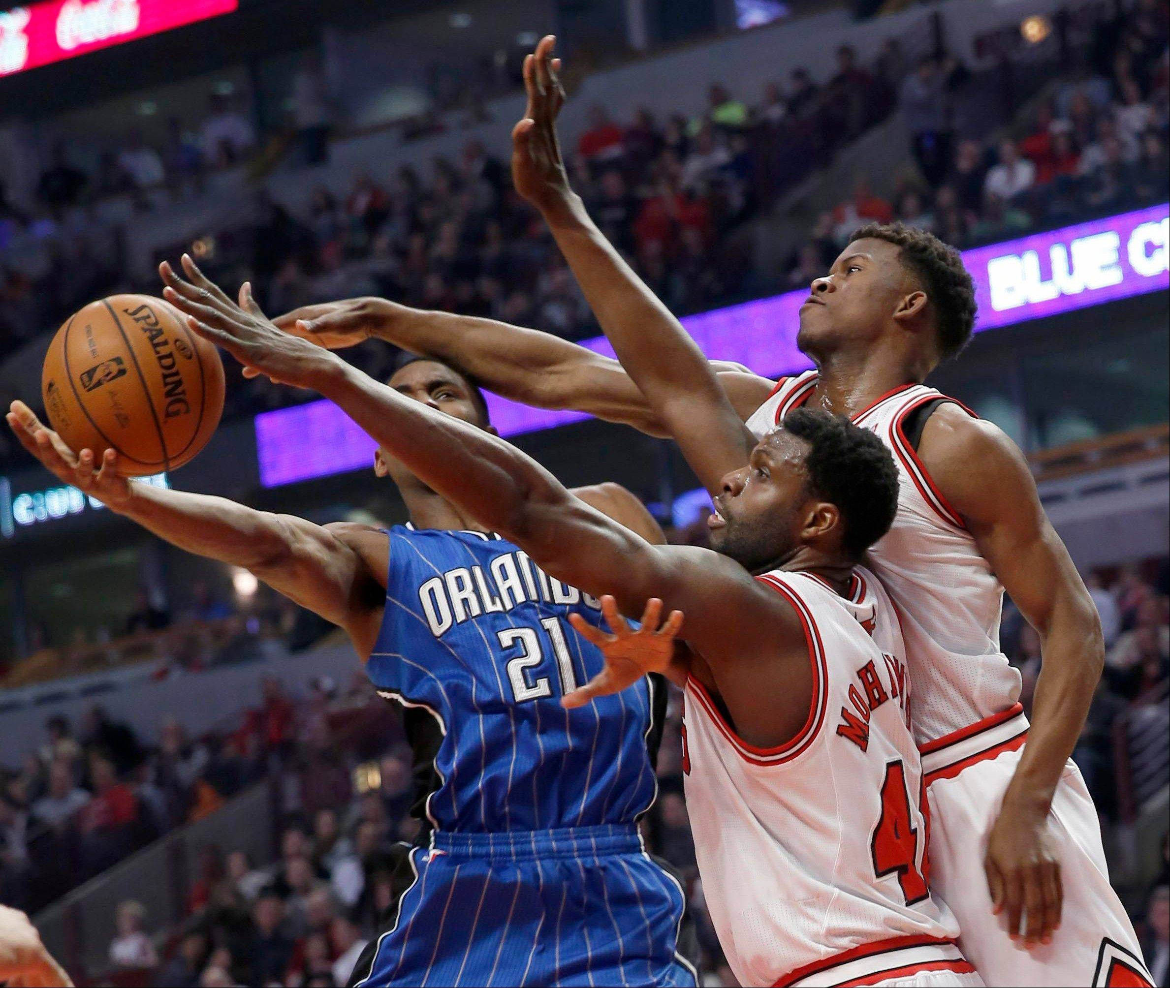 Nazr Mohammed, front, and Jimmy Butler defend Orlando Magic�s Maurice Harkless during the first half of the Bulls� victory Friday at the United Center.