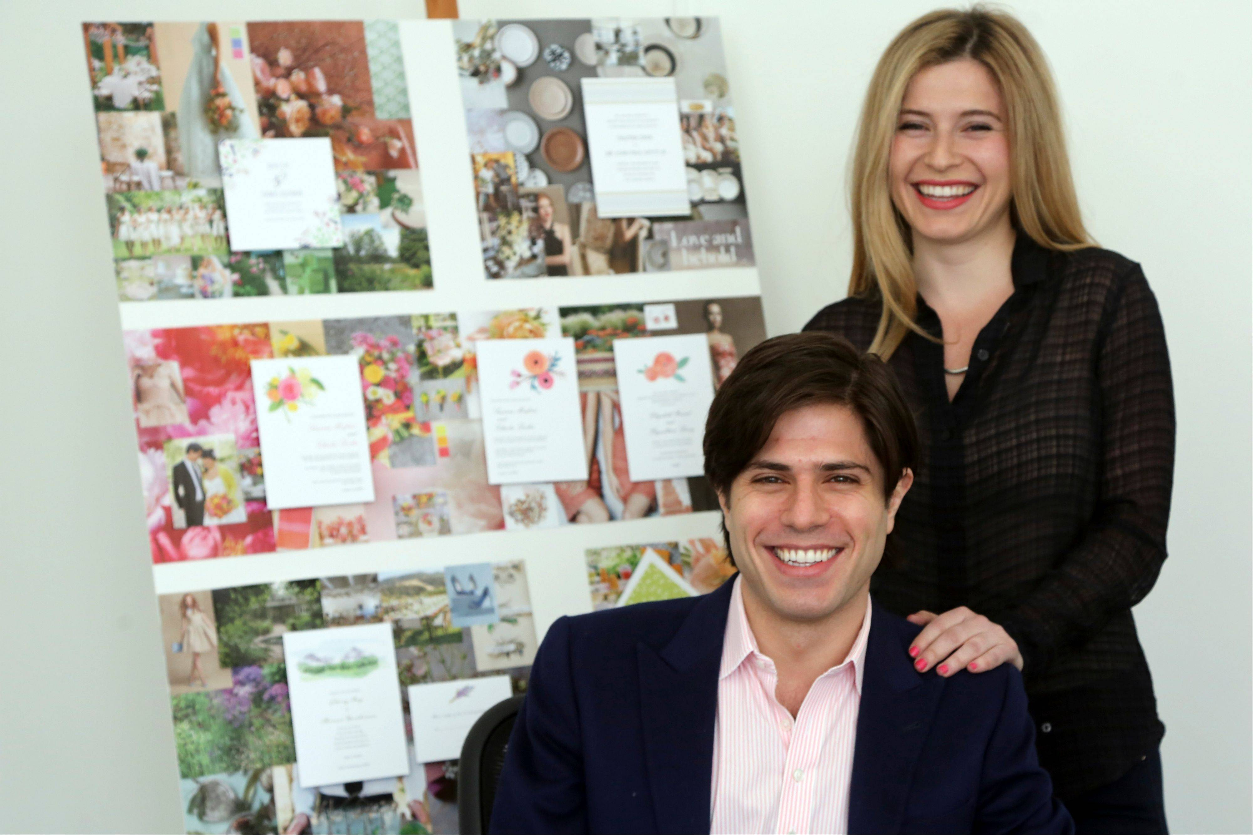 In this Friday, March 29, 2013 photo Alexa Hirschfeld, right, and James Hirschfeld smile as they pose for a photo at their office in New York. Paperless Post has defied its original digital business model successfully once. Now the online invitation and greeting card startup is taking that defiance a step further. The New Yaork company launched PAPER by Paperless Post in October after customers requested a way to get its electronic greeting cards and invitations in a more old-fashioned way: On actual paper. Now Paperless Post is teaming up with stationery.